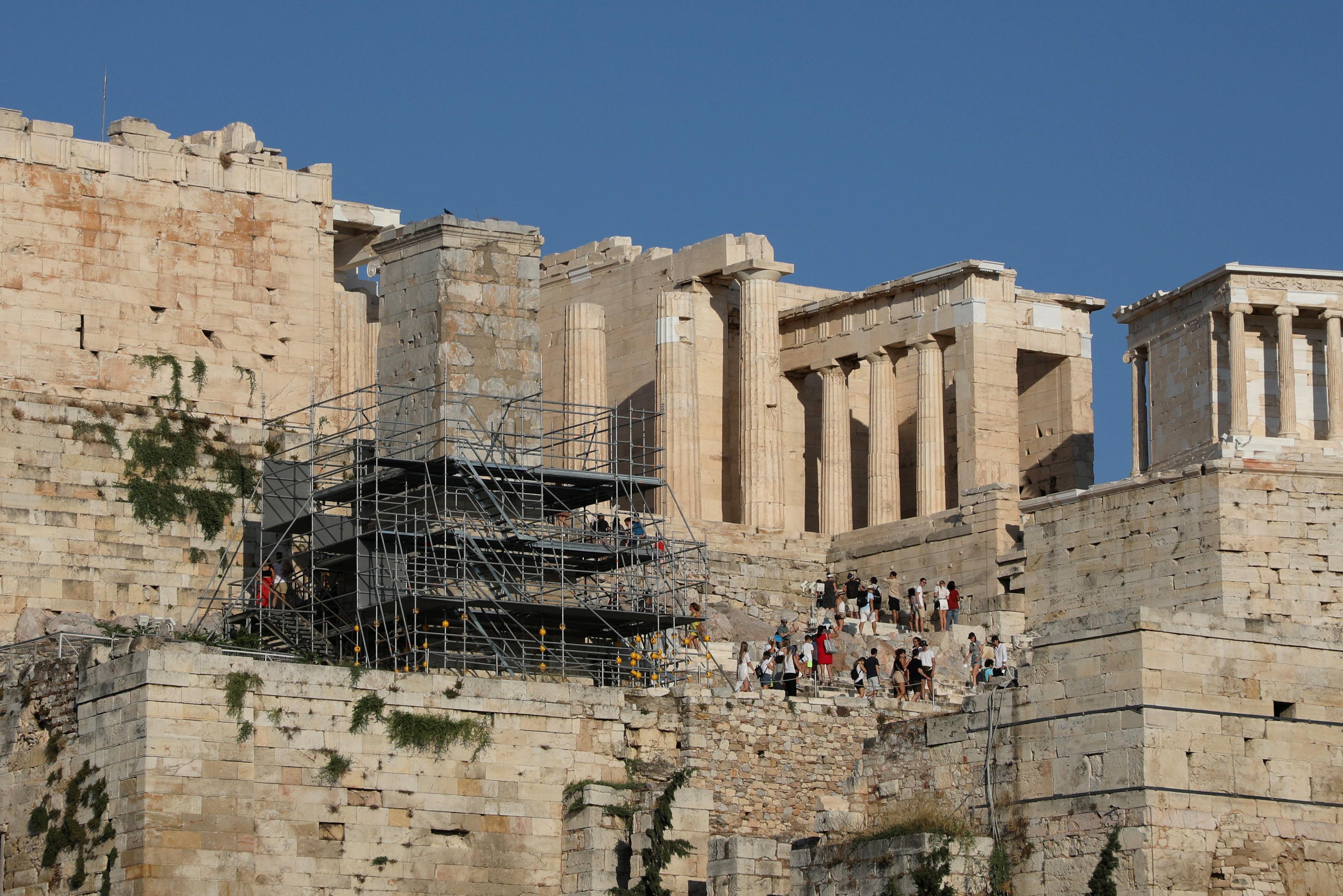 ტურისტები გეზი მიდიან პროპილაიასთან, აკროპოლისის მახლობლად, ათენის დედაქალაქ საბერძნეთში, 25 ივლისი, 2021 ივლისი. სურათი გადაღებულია 25 წლის 2021 ივლისს. REUTERS / ლუიზა ვრადი