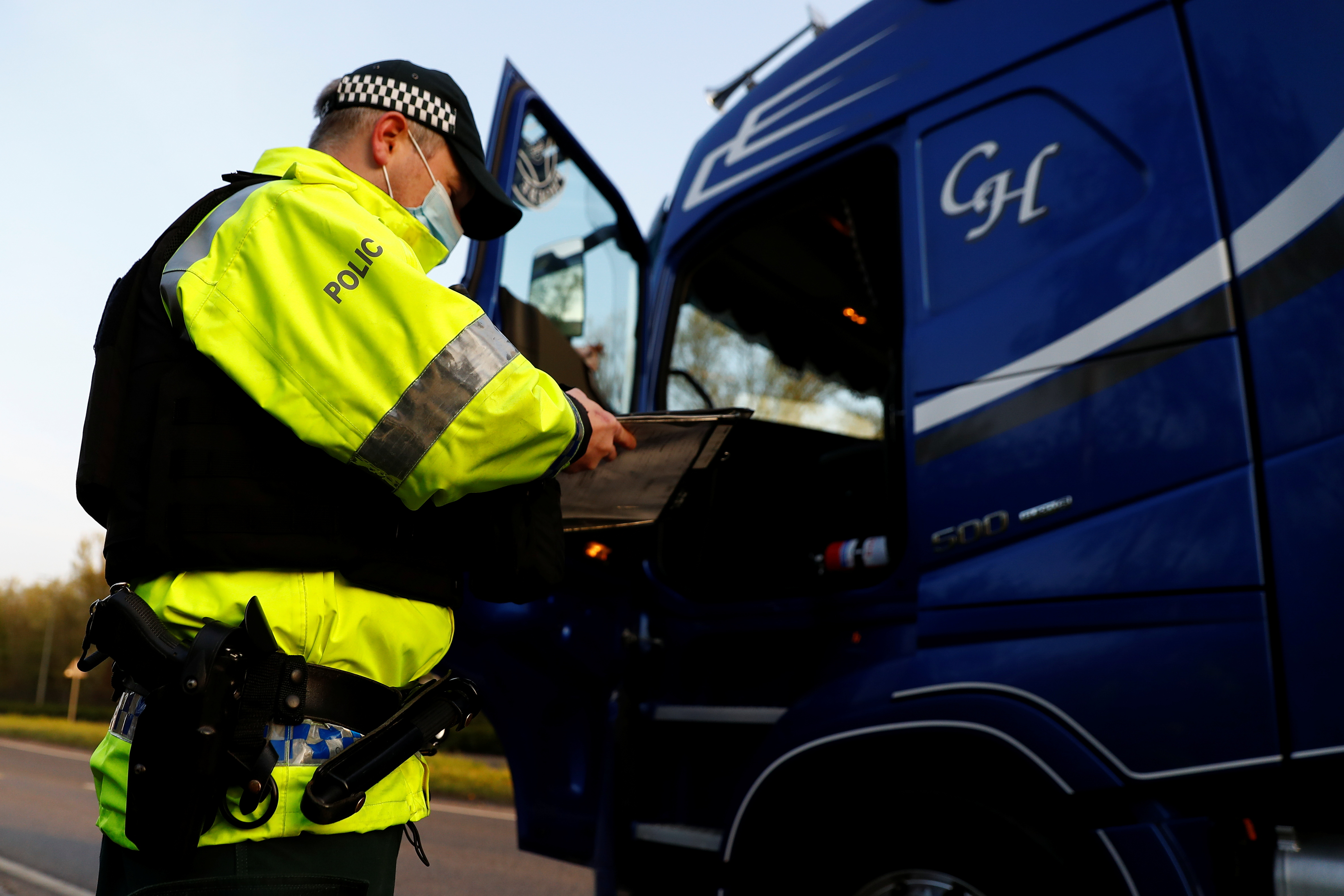 A police officer checks a truck during a joint operation by the Police Service of Northern Ireland (PSNI), Driver Vehicle Agency goods enforcement division and Her Majesty's Revenue and Customs (HMRC), at Belfast Port, Northern Ireland April 22, 2021. REUTERS/Jason Cairnduff