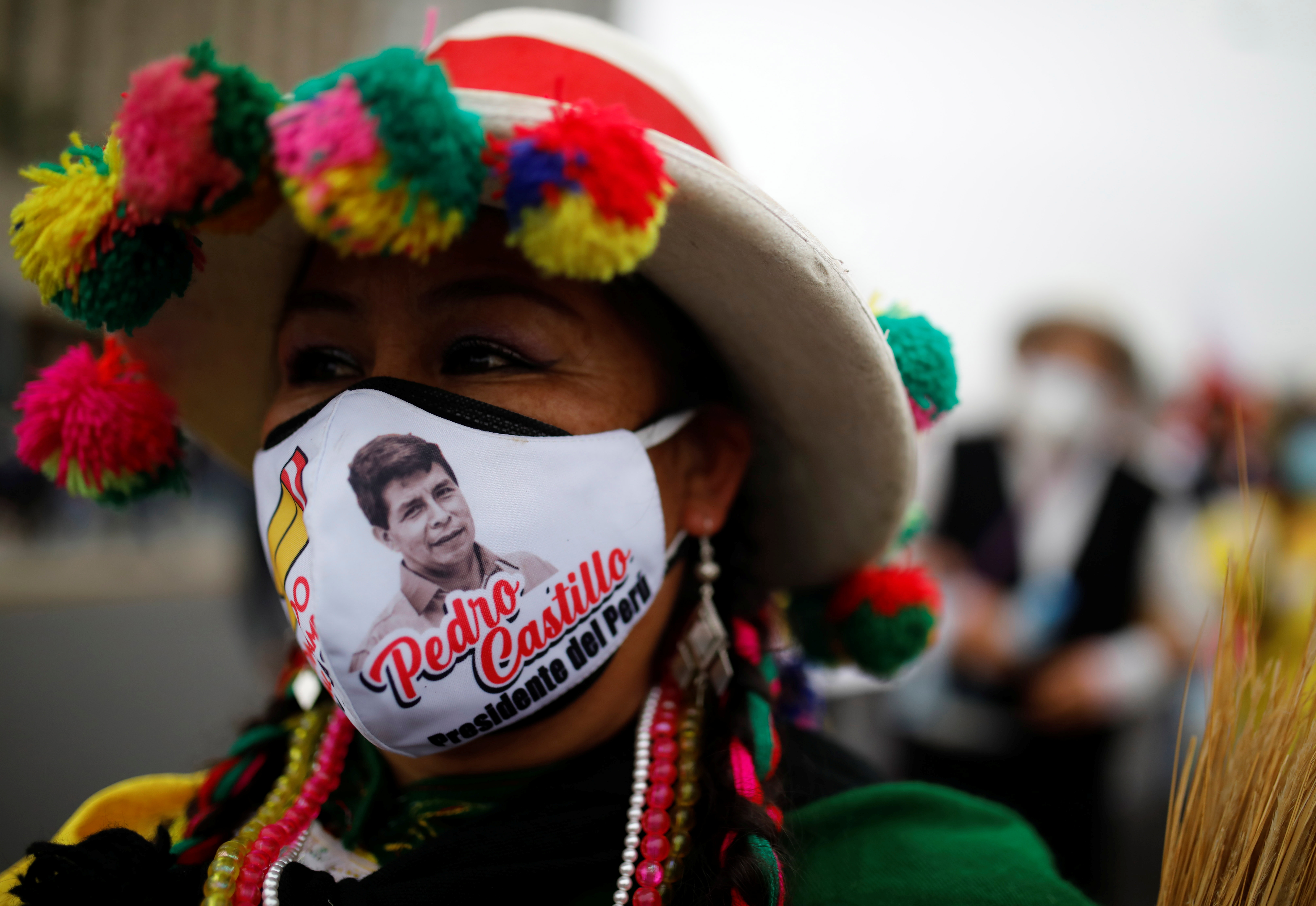 A supporter wearing a face mask with the image of Peru's presidential candidate Pedro Castillo marches in Lima, Peru June 26, 2021. REUTERS/Sebastian Castaneda