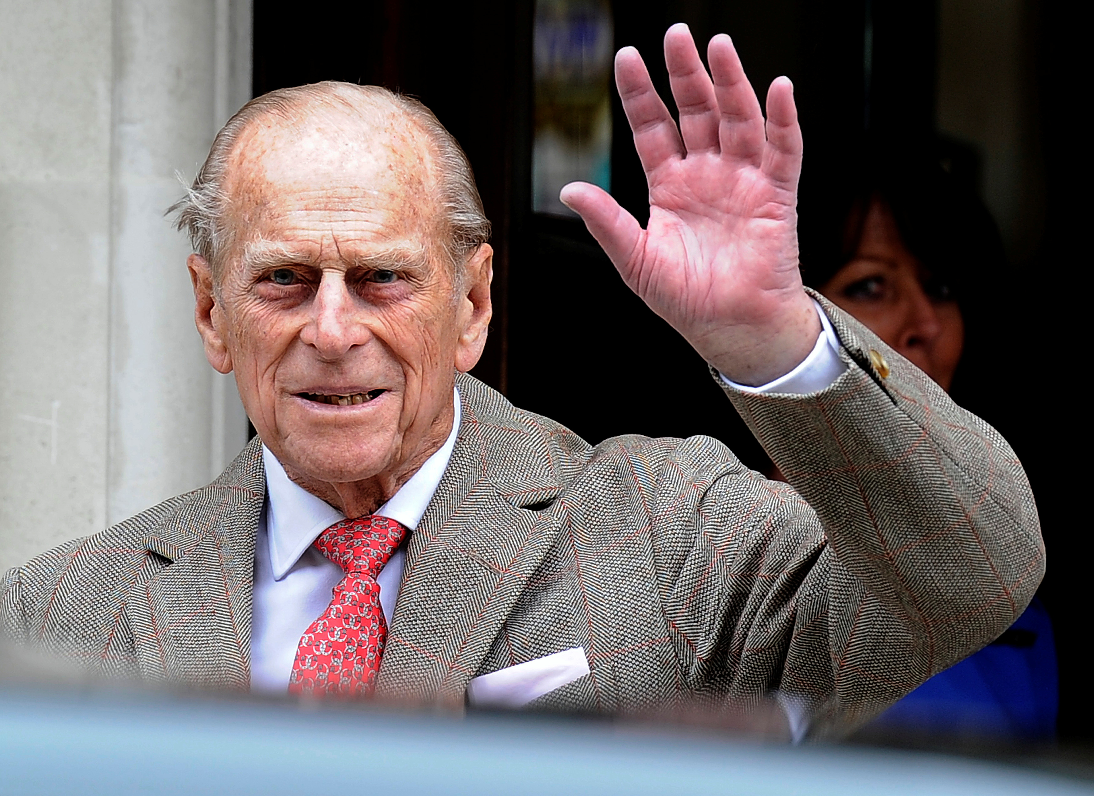 Britain's Prince Philip waves to members of the media as he leaves the King Edward VII Hospital in London June 9, 2012. REUTERS/Paul Hackett/File Photo