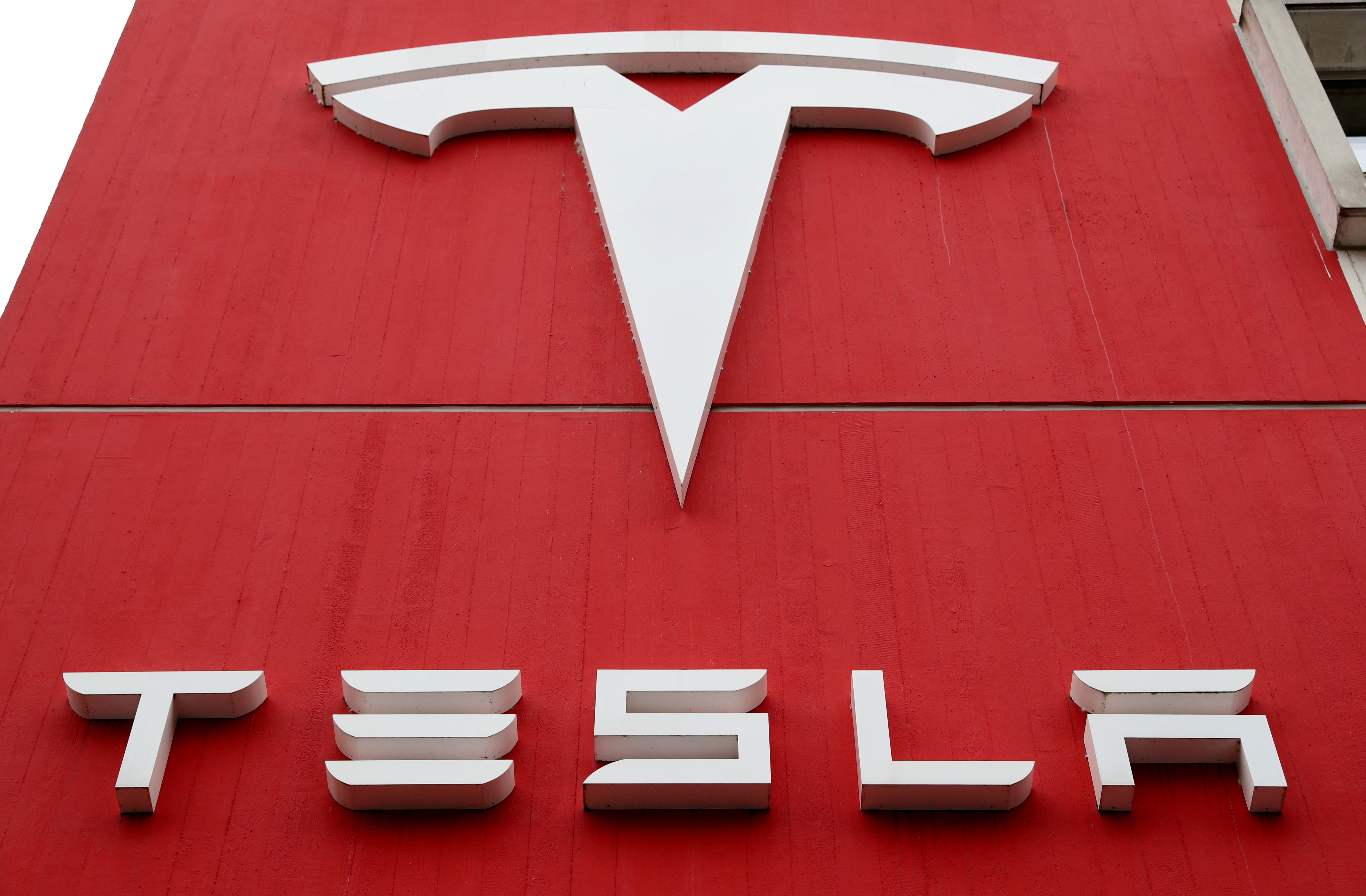 FILE PHOTO: The logo of car manufacturer Tesla is seen at a branch office in Bern, Switzerland October 28, 2020. REUTERS/Arnd Wiegmann/File Photo/File Photo