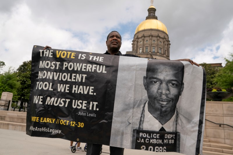 Robin Donaldson holds a banner with he voting quote and photo of John Lewis during a rally against the state's new voting restrictions outside the Georgia State Capitol, in Atlanta, Georgia, U.S., June 8, 2021. REUTERS/Elijah Nouvelage/File Photo