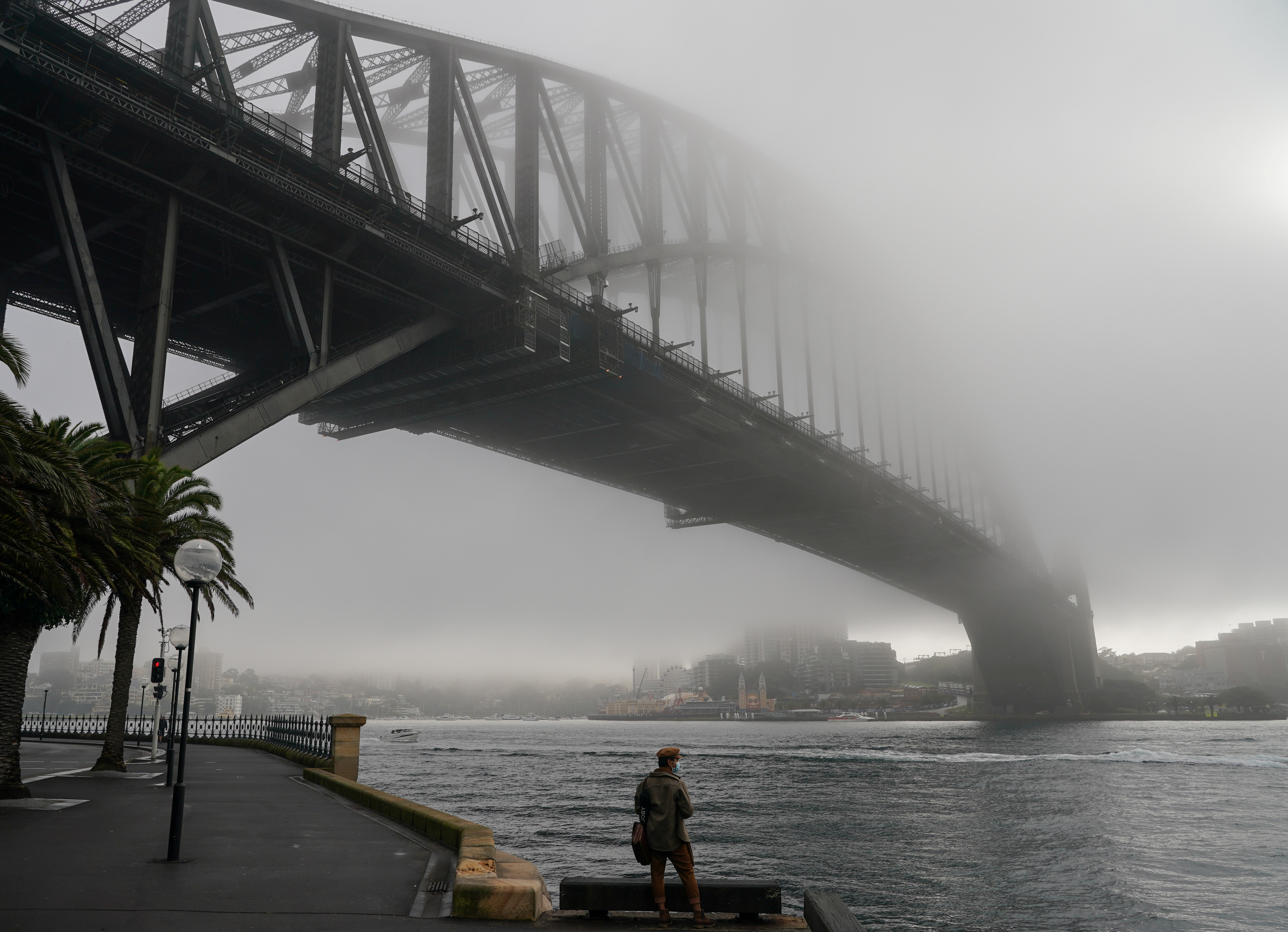 A man wearing a protective face mask takes in the waterfront view underneath the Sydney Harbour Bridge, seen shrouded in fog, during a lockdown to curb the spread of a coronavirus disease (COVID-19) outbreak in Sydney, Australia, June 30, 2021. REUTERS/Loren Elliott