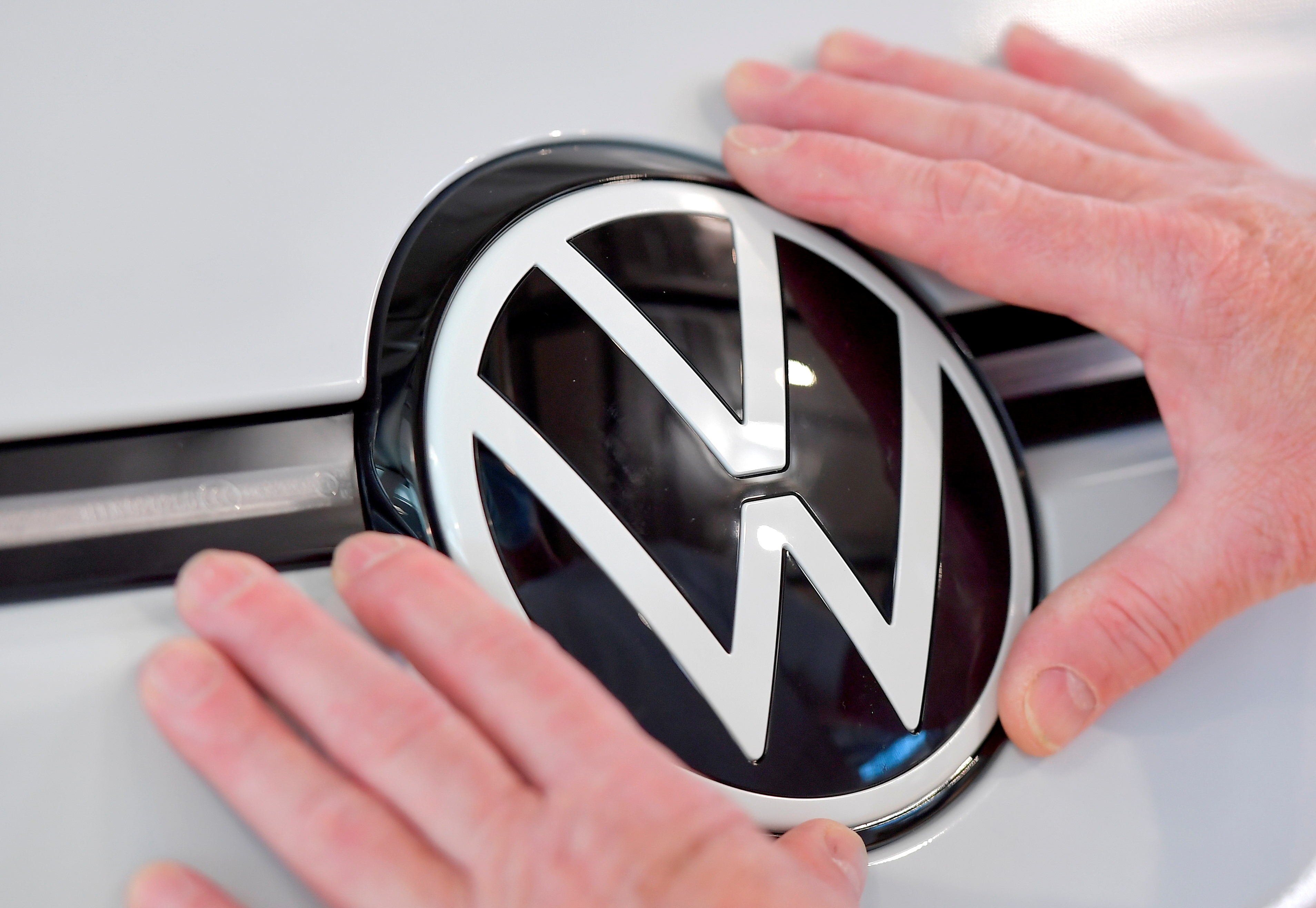 A technician fixes a VW sign in the assembly line of German carmaker Volkswagen's electric ID. 3 car in Dresden, Germany, June 8, 2021. REUTERS/Matthias Rietschel