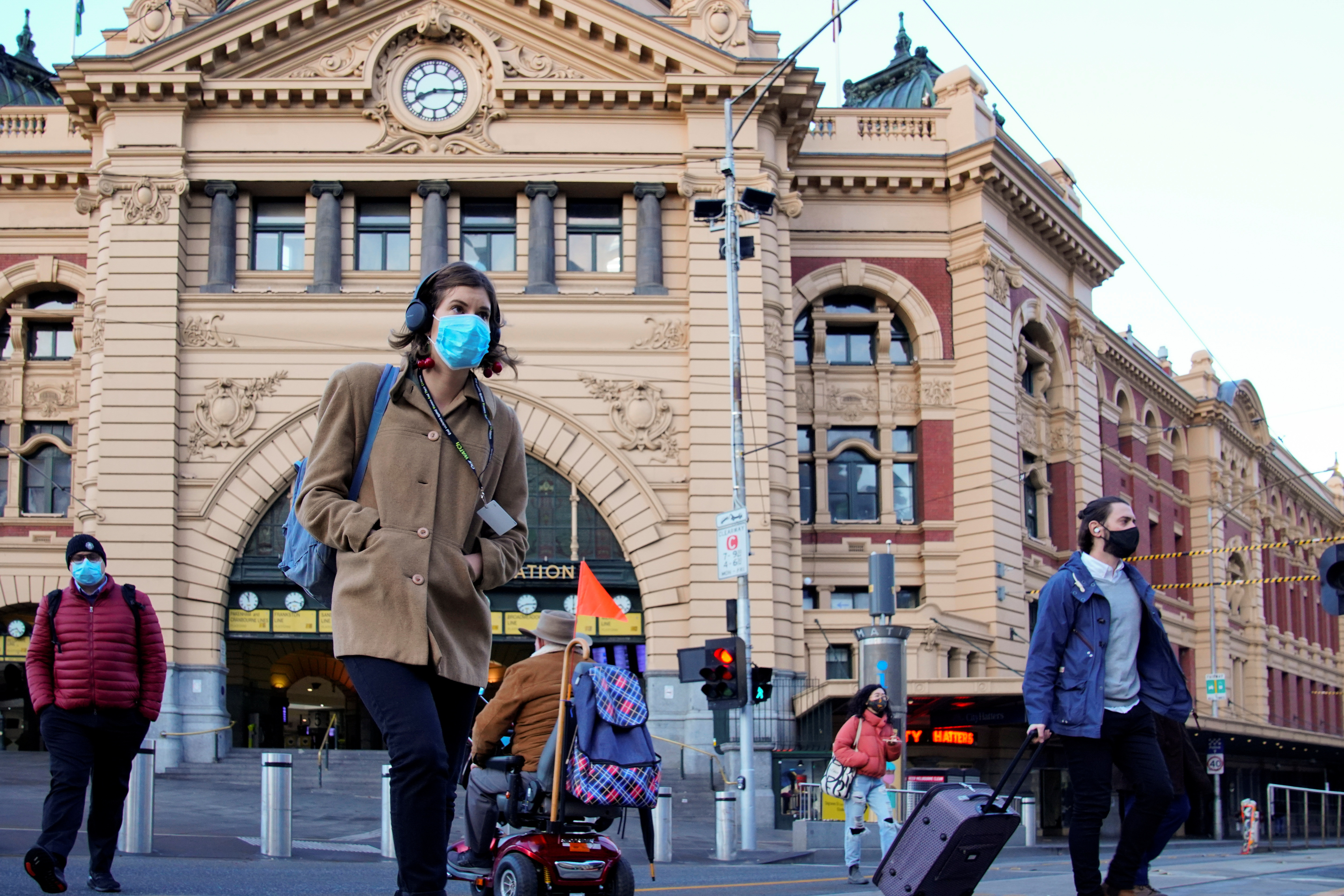 Pedestrians cross the road at Flinders Street Station on the first day of eased coronavirus disease (COVID-19) restrictions for the state of Victoria following an extended lockdown in Melbourne, Australia, June 11, 2021.  REUTERS/Sandra Sanders