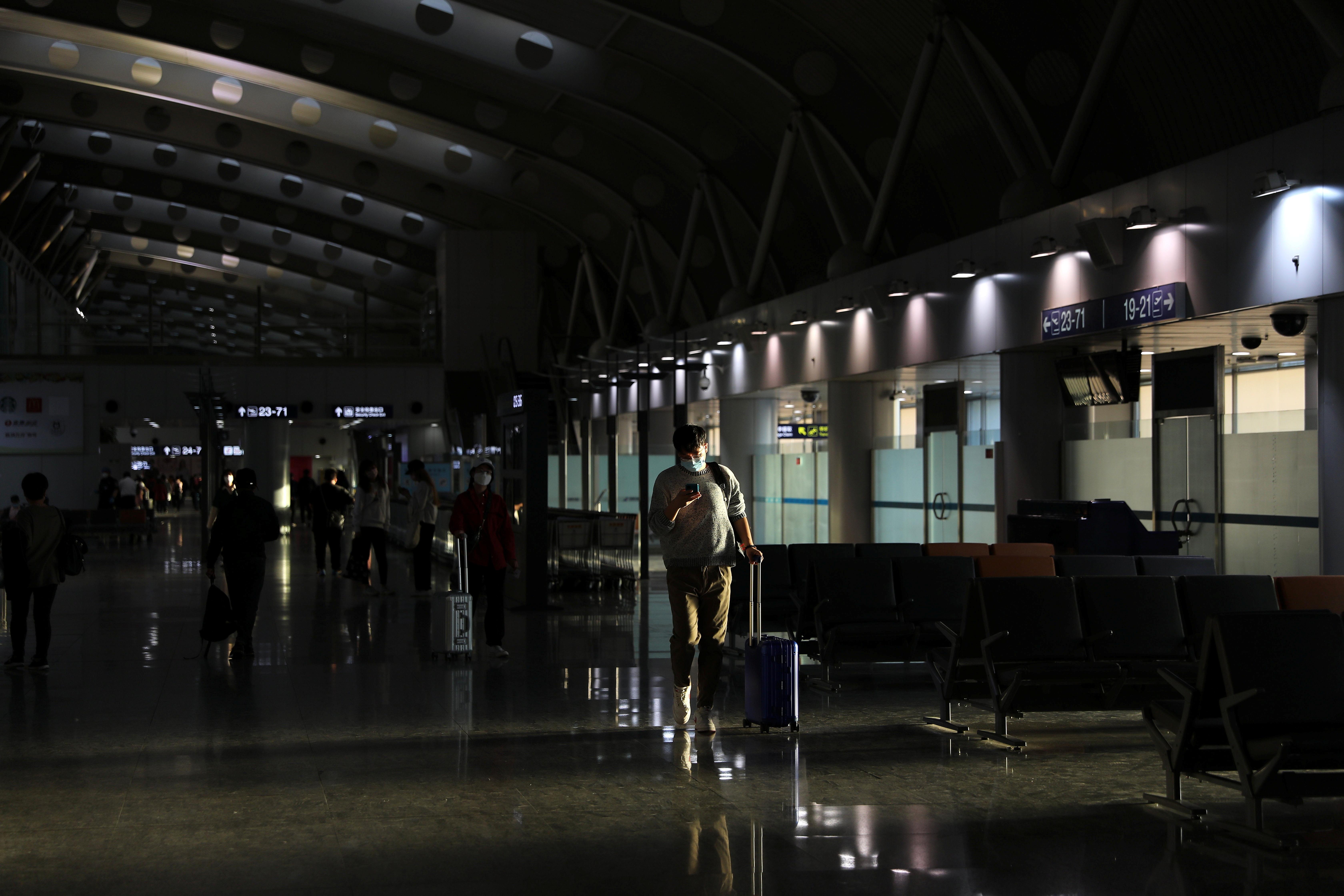 A traveller walks at the Beijing Capital International Airport in Beijing, China May 9, 2021. REUTERS/Tingshu Wang