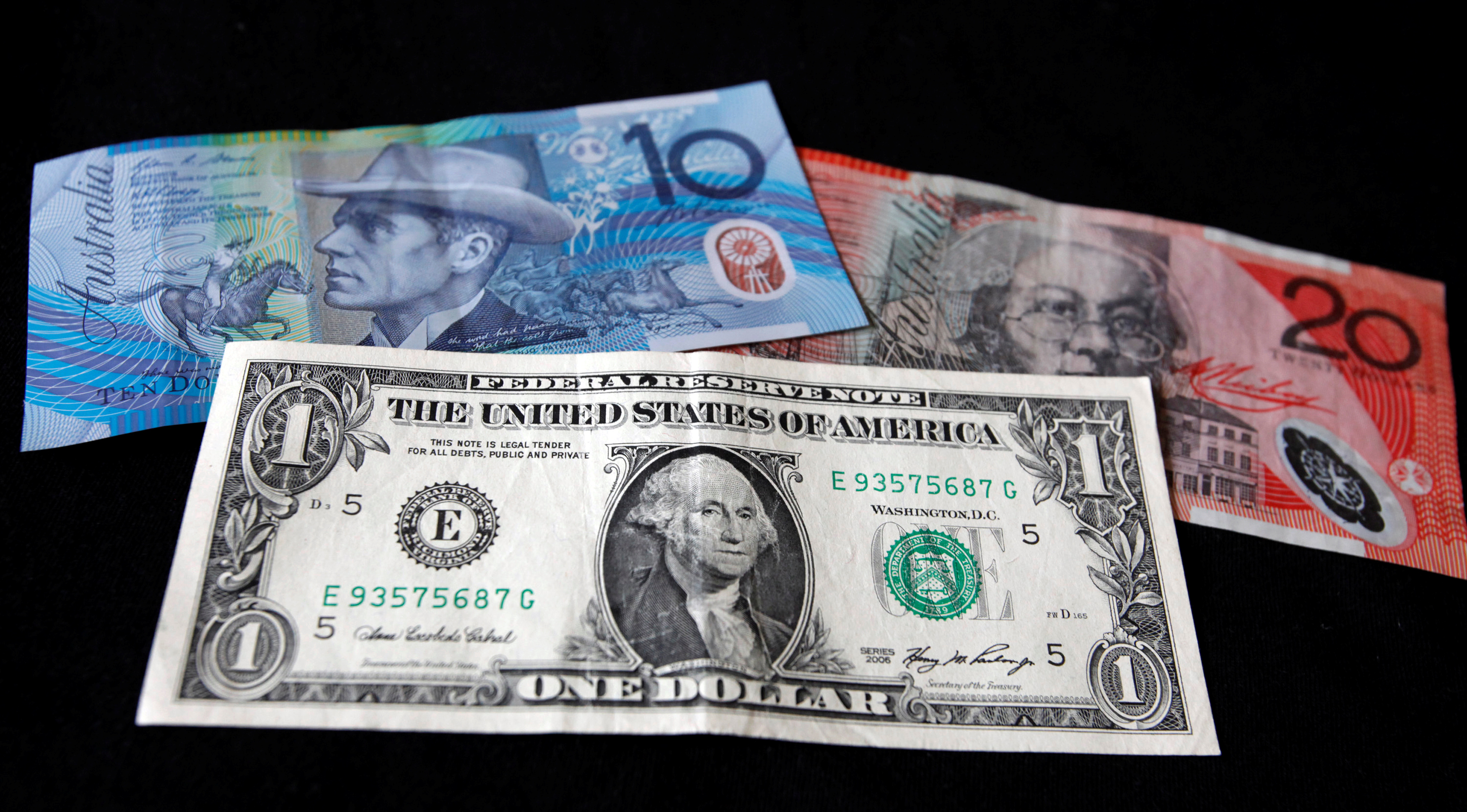 A U.S. dollar note (bottom) is pictured alongside an Australian 10 dollar (L) and 20 dollar bill in this picture illustration taken in Washington, October 14, 2010.  REUTERS/Jason Reed/File Photo