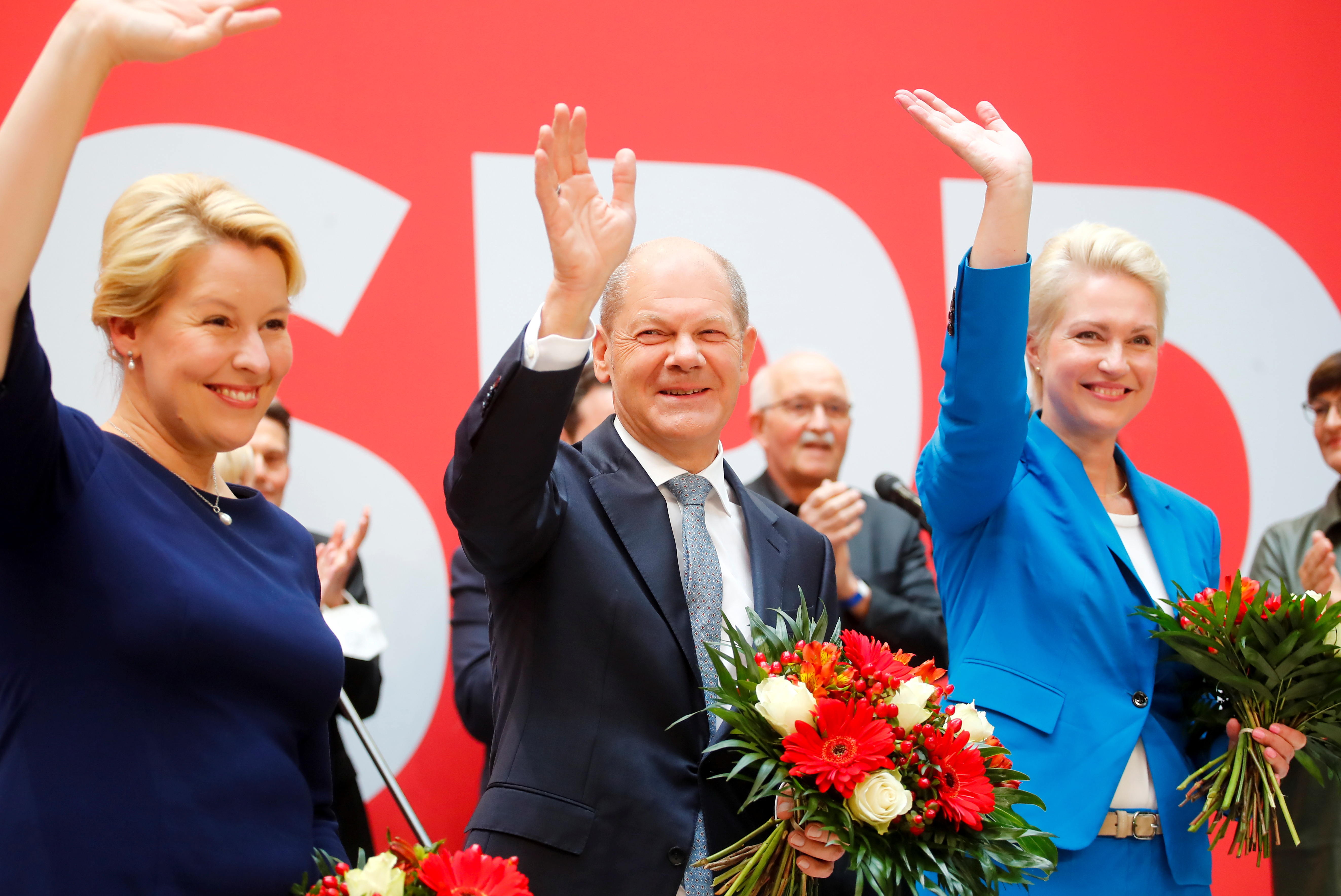Social Democratic Party (SPD) leader and top candidate for chancellor Olaf Scholz, Mecklenburg-Western Pomerania state Prime Minister Manuela Schwesig and SPD member Franziska Giffey wave as they carry bouquets of flowers at their party leadership meeting, one day after the German general elections, in Berlin, Germany, September 27, 2021. REUTERS/Wolfgang Rattay