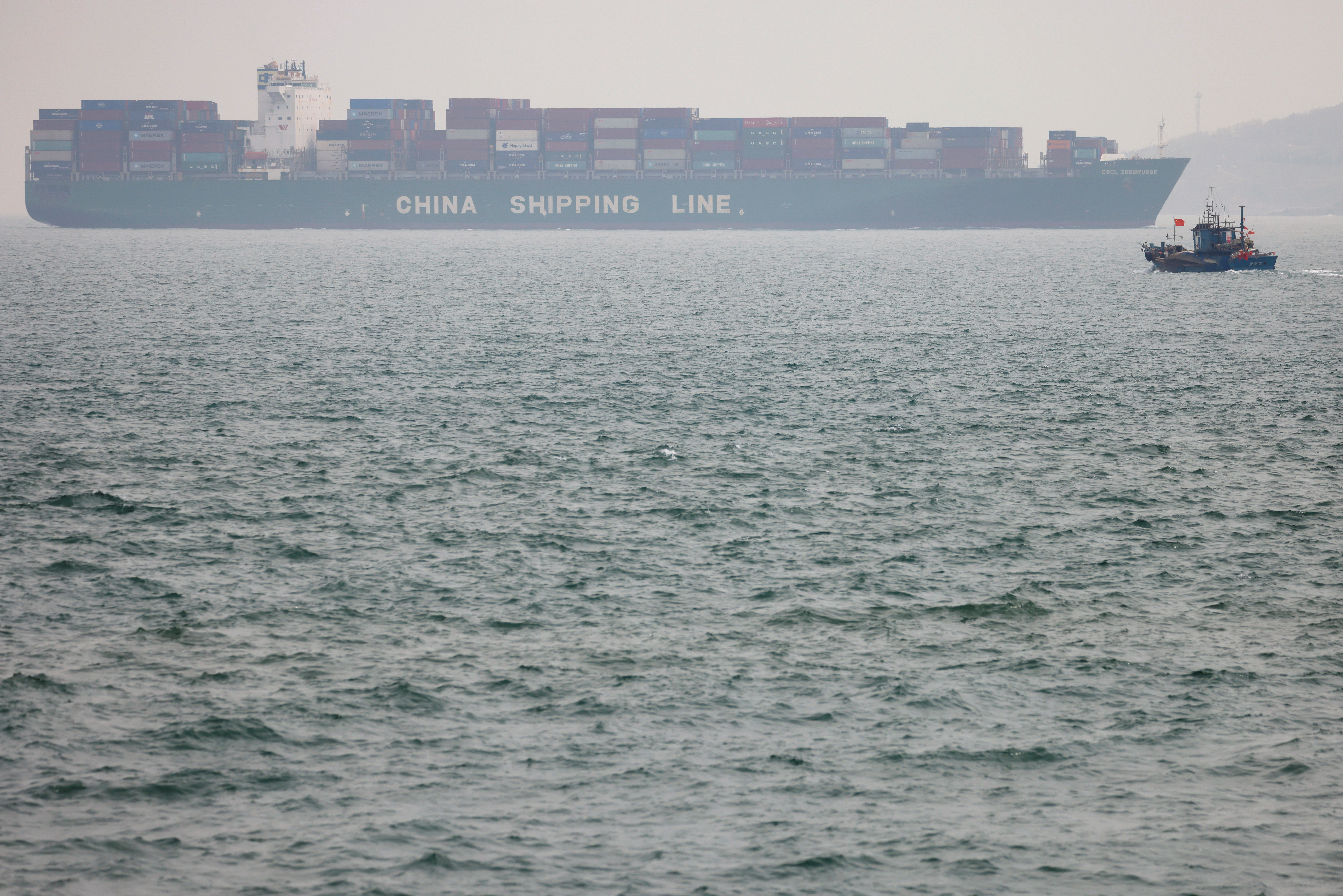A fishing boat is seen near a China Shipping Container Lines (CSCL) vessel off the coast of Qingdao, Shandong province, China, following an oil spill in the Yellow Sea caused by a collision between tanker A Symphony and bulk vessel Sea Justice off Qingdao port,April 29, 2021. REUTERS/Carlos Garcia Rawlins