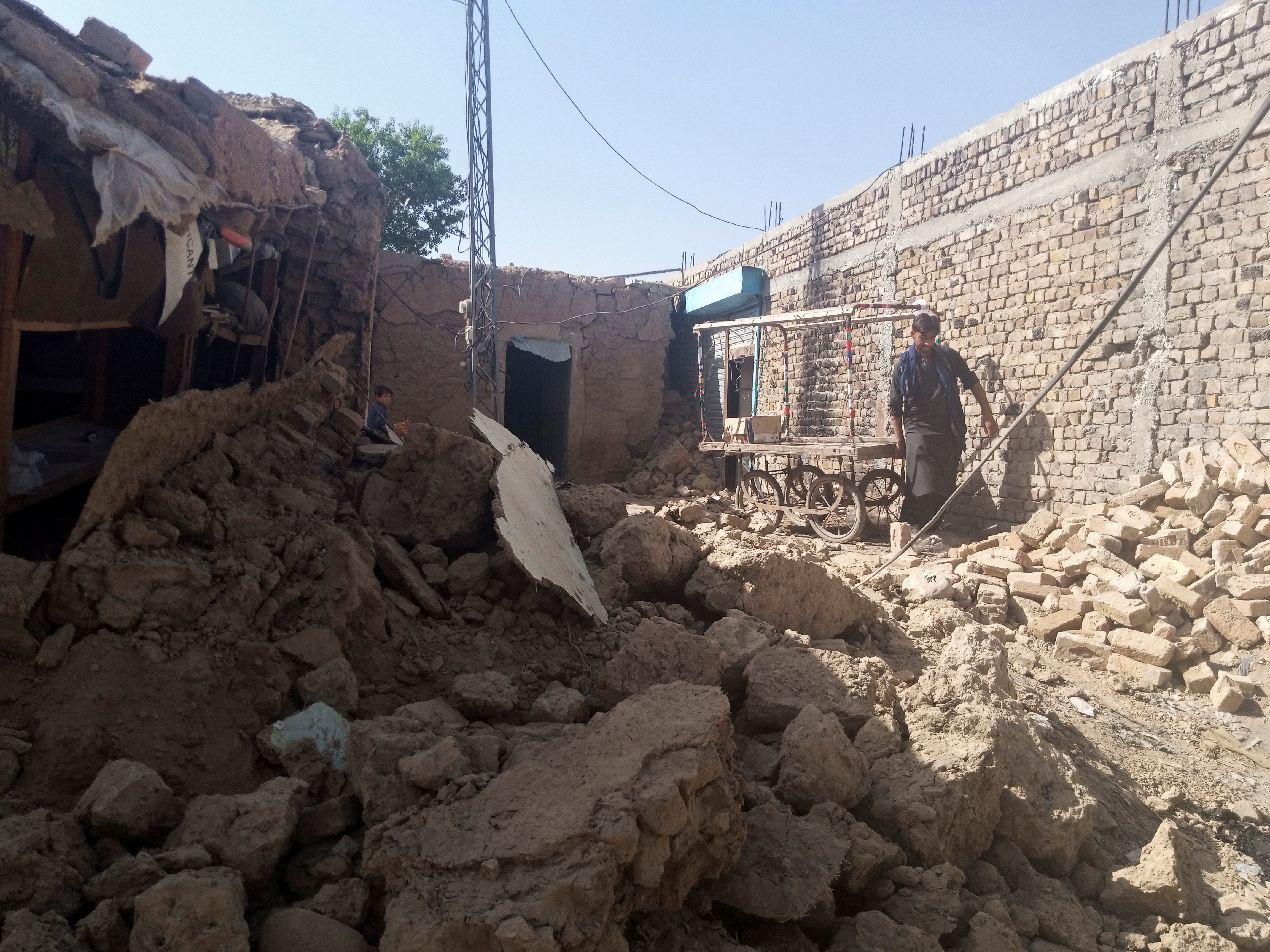 A man removes his pushcart from the rubble of a damaged house following an earthquake in Harnai, Balochistan, Pakistan, October 7, 2021. REUTERS/Naseer Ahmed