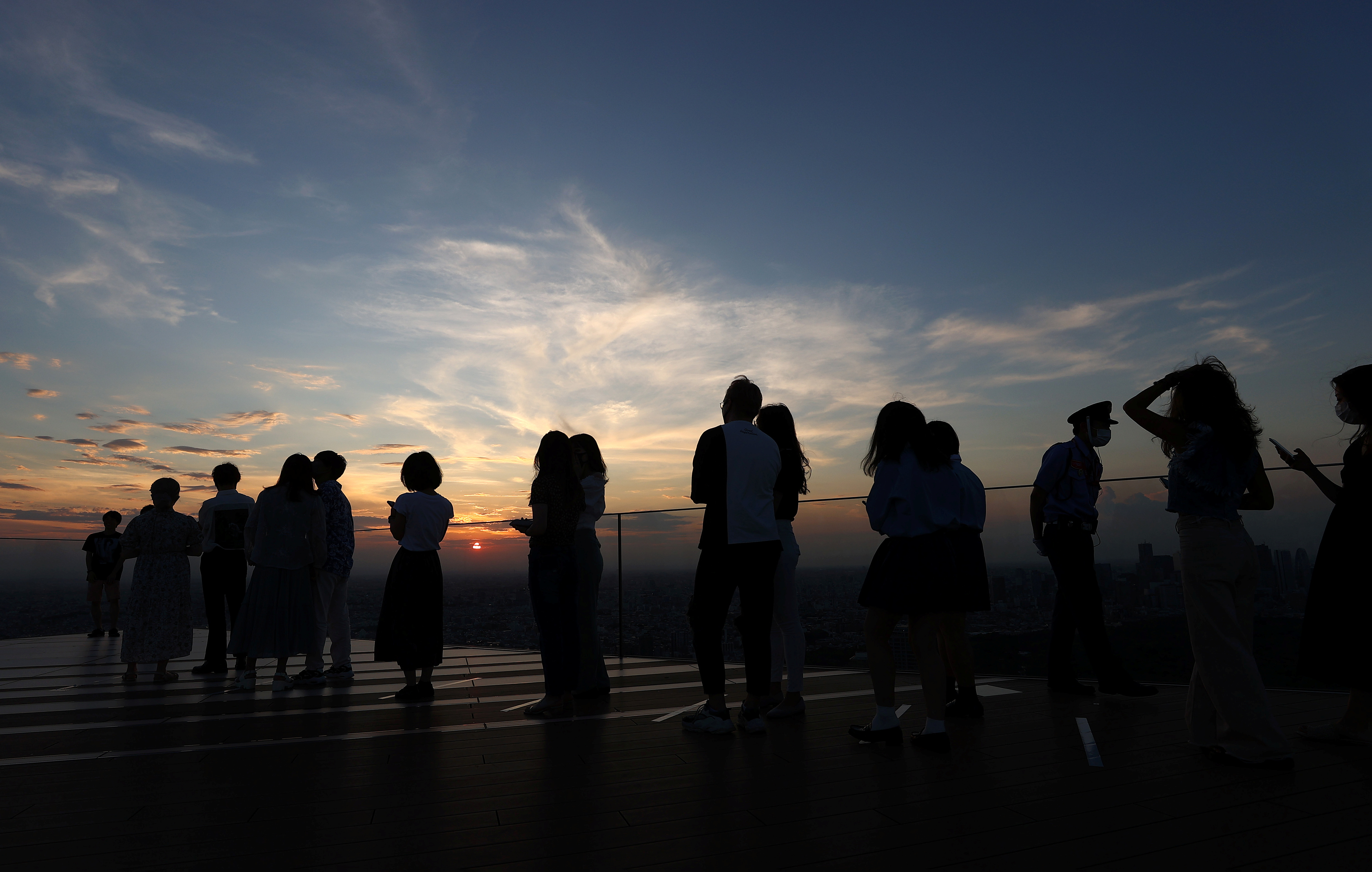 People queue up to get their picture taken in front of the sunset on top of Shibuya Sky observation deck, ahead of the Tokyo 2020 Olympic Games, in Tokyo, Japan, July 19, 2021.   REUTERS/Kai Pfaffenbach