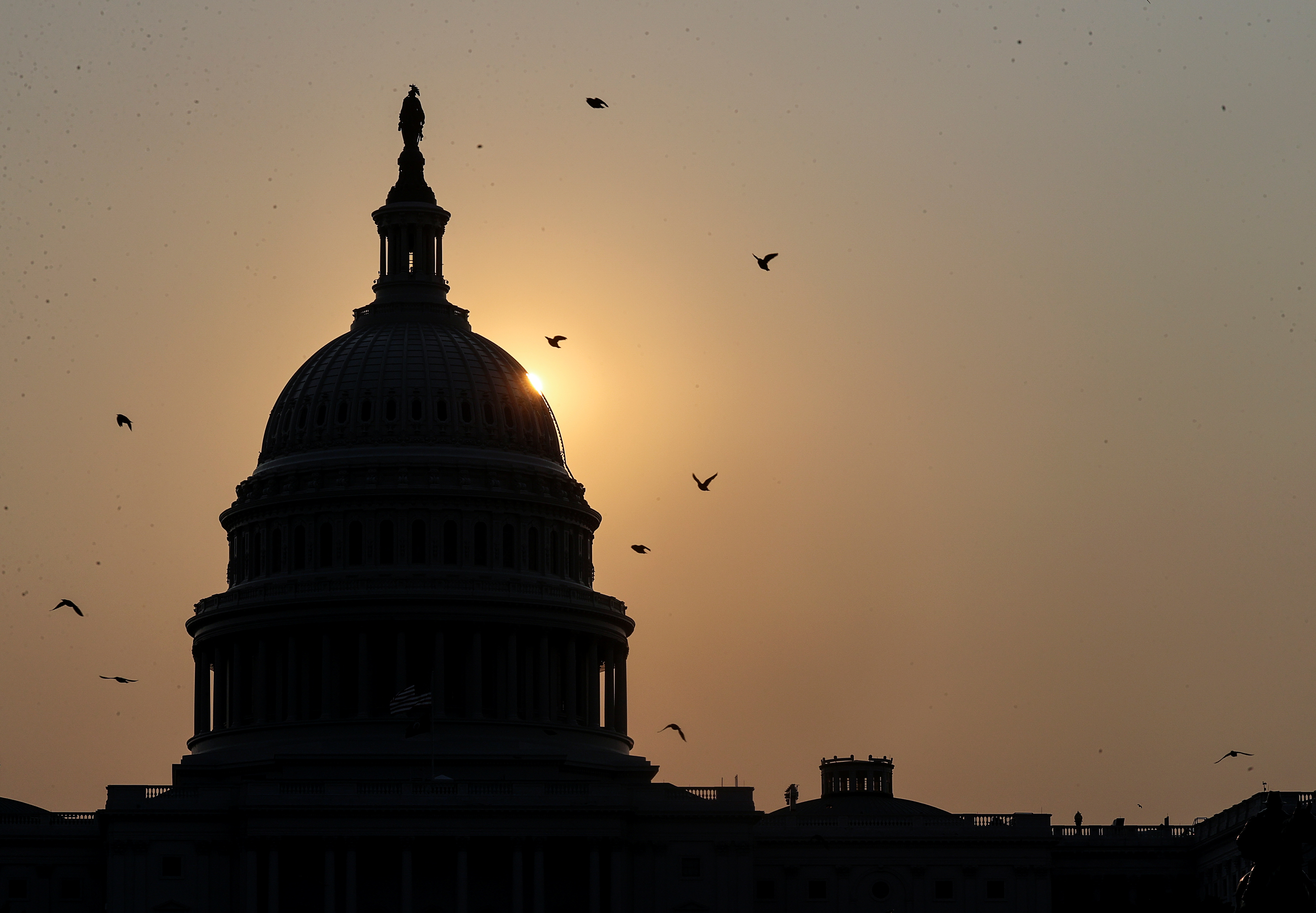 FILE PHOTO: The sun rises behind U.S. Capitol ahead of a weekend