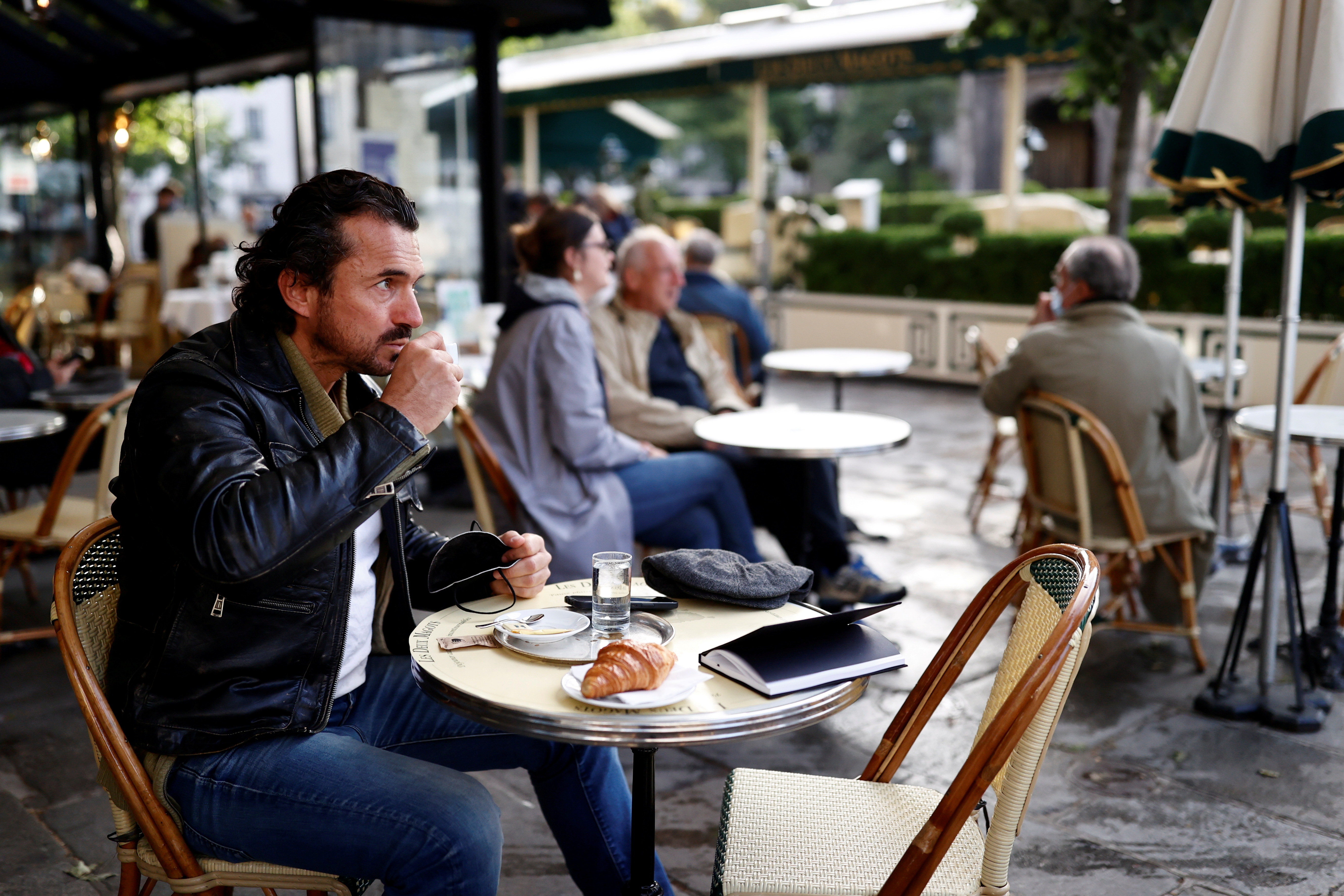 A customer enjoys a coffee on a terrace of the cafe and restaurant Les Deux Magots in Paris as cafes, bars and restaurants reopen after closing down for months amid the coronavirus disease (COVID-19) outbreak in France, May 19, 2021. REUTERS/Christian Hartmann