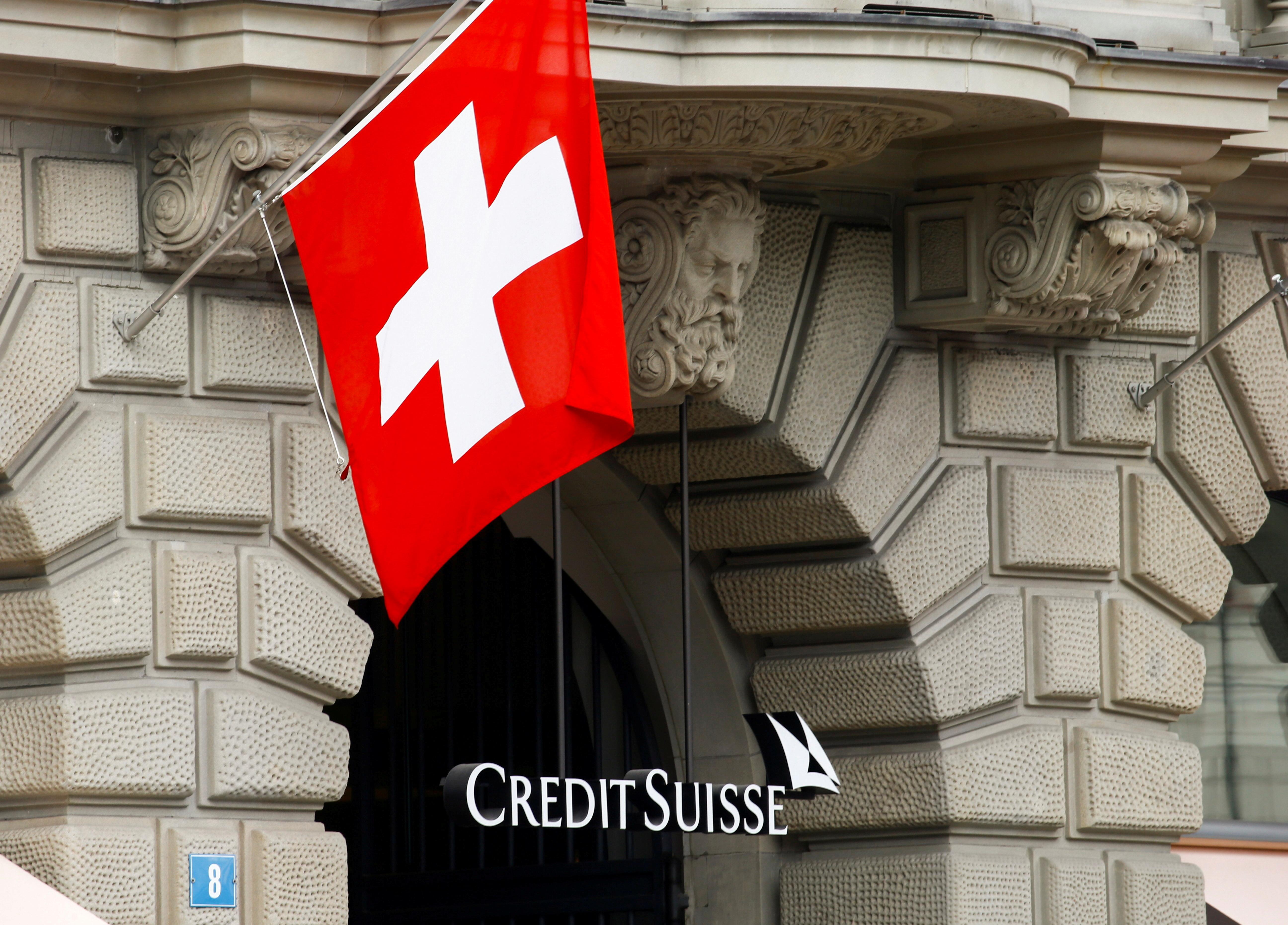 Switzerland's national flag flies above the logo of Swiss bank Credit Suisse at its headquarters in Zurich, Switzerland April 18, 2021. REUTERS/Arnd Wiegmann/File Photo