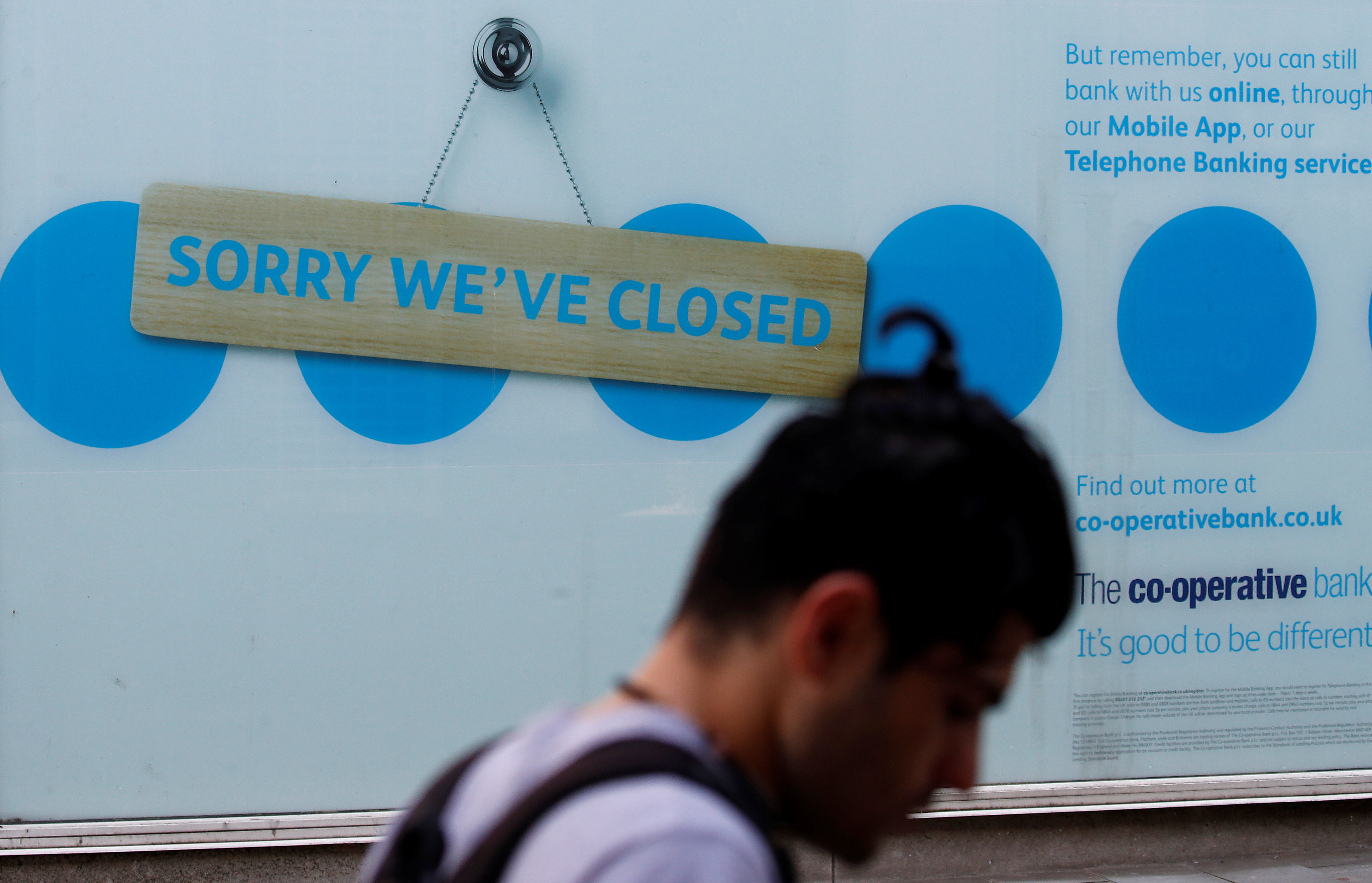 A man walks past a closed branch of the Co-Operative bank following the outbreak of the coronavirus disease (COVID-19) in St Helens, Britain, August 12, 2020. REUTERS/Phil Noble