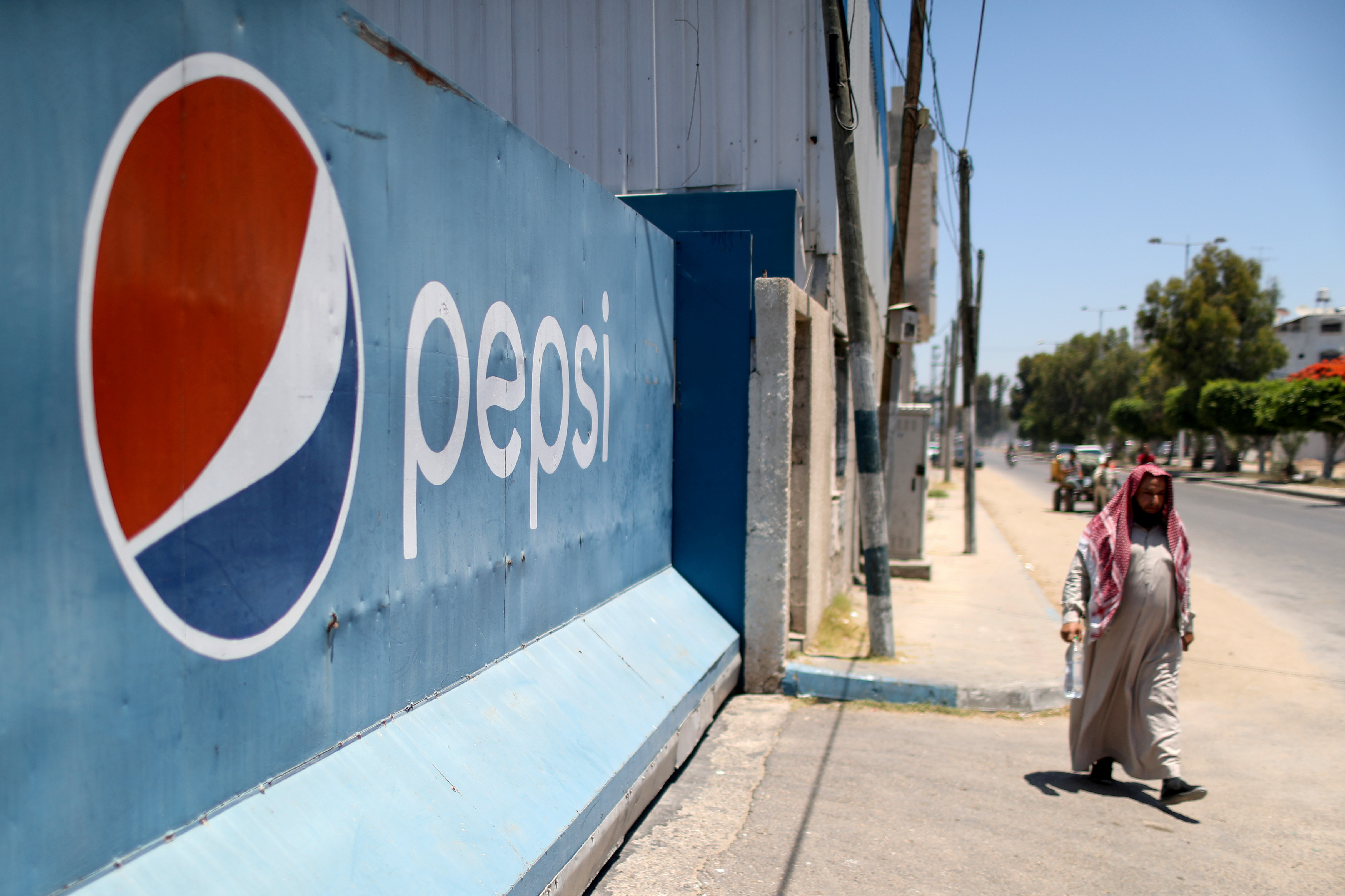 A Palestinian man walks past Gaza Pepsi factory for soft drinks in Gaza City June 21, 2021. REUTERS/Mohammed Salem