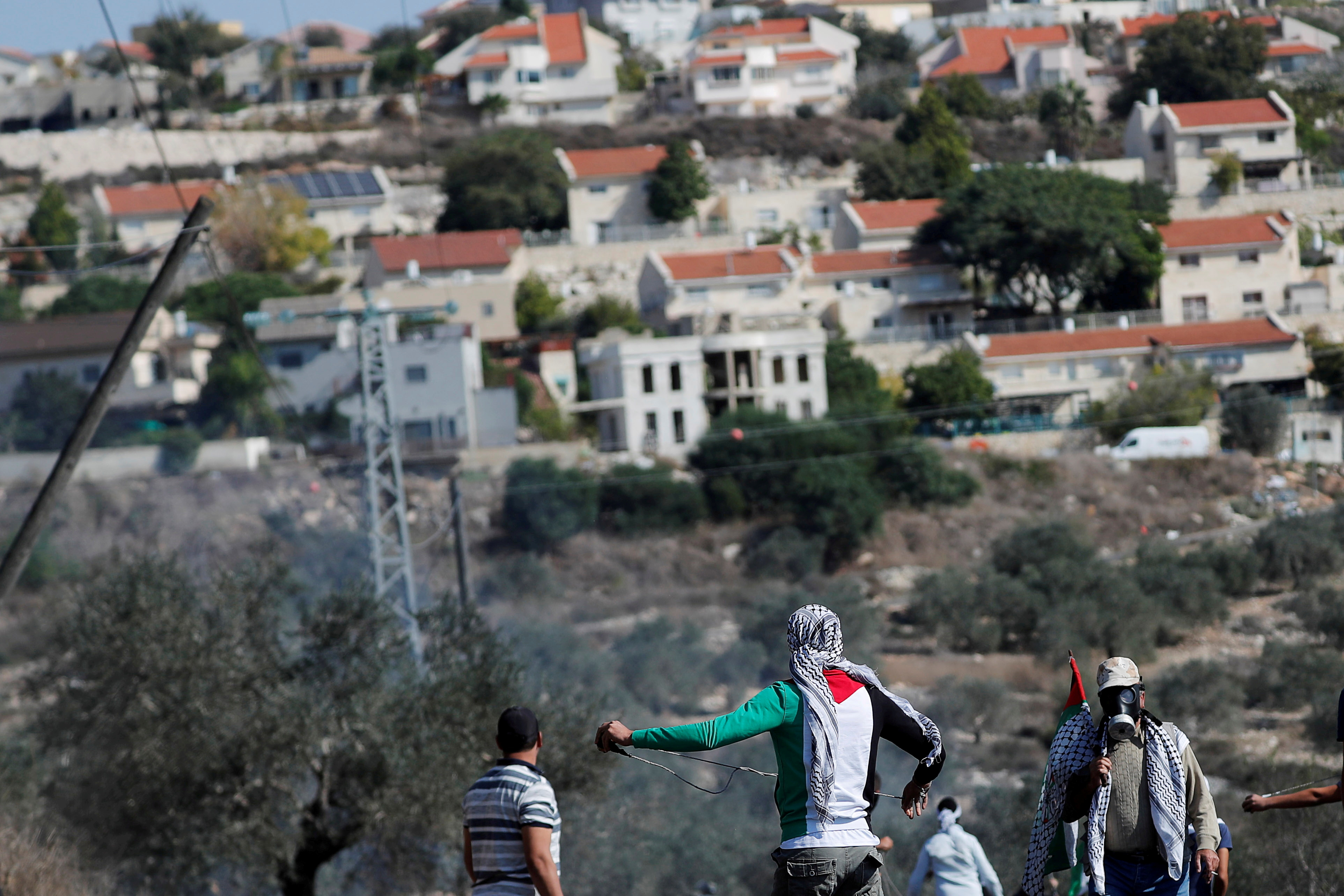 Palestinian demonstrators stand in front of a Jewish settlement during a protest, in Kafr Qaddum in the Israeli-occupied West Bank November 13, 2020. REUTERS/Mohamad Torokman/File Photo