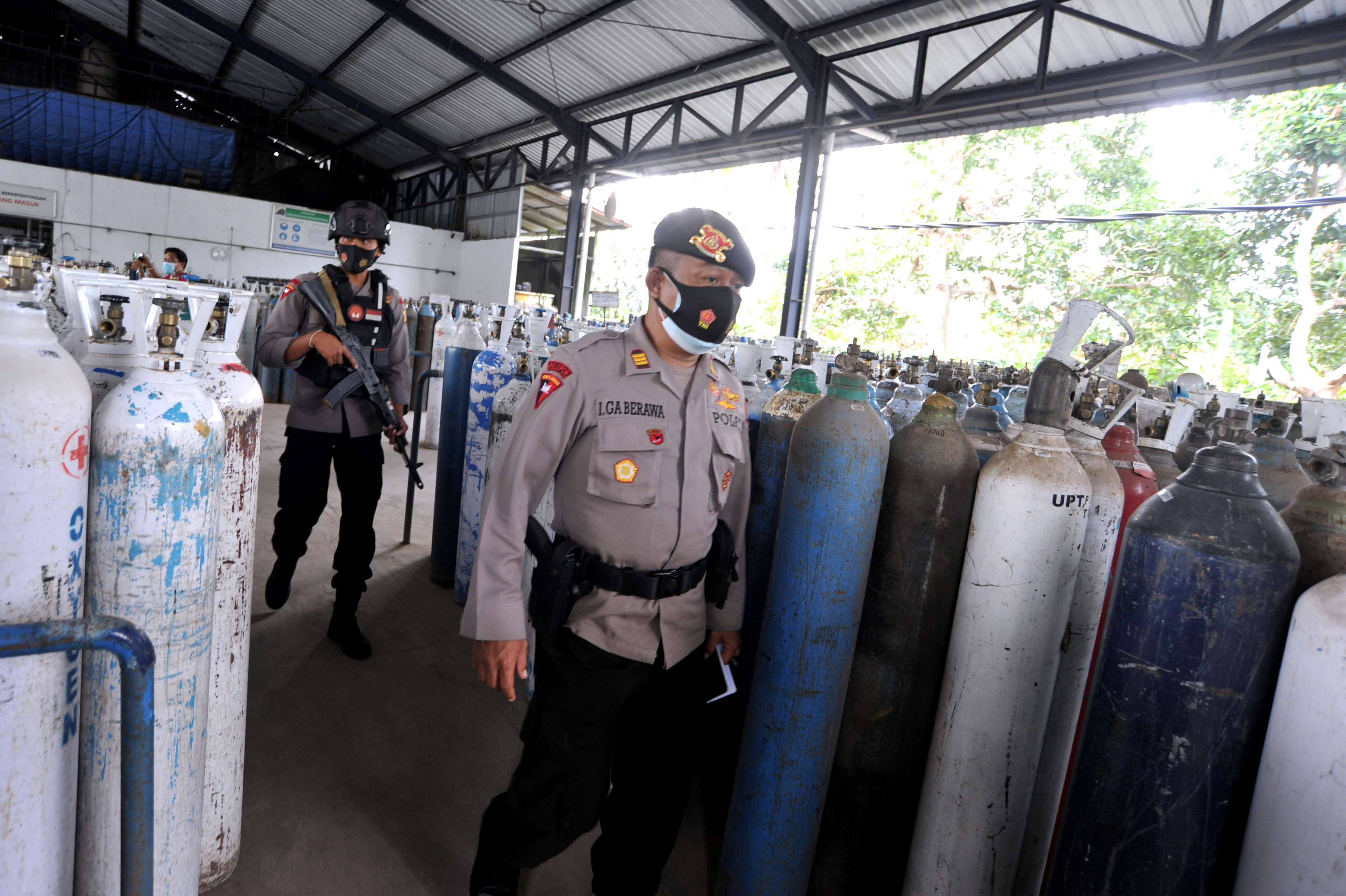 Police officers walk as they guard the oxygen distribution at a refill factory amid the coronavirus disease (COVID-19) outbreak in Mengwi, Badung, Bali, Indonesia, July 22, 2021, in this photo taken by Antara Foto. Antara Foto/Fikri Yusuf/ via REUTERS