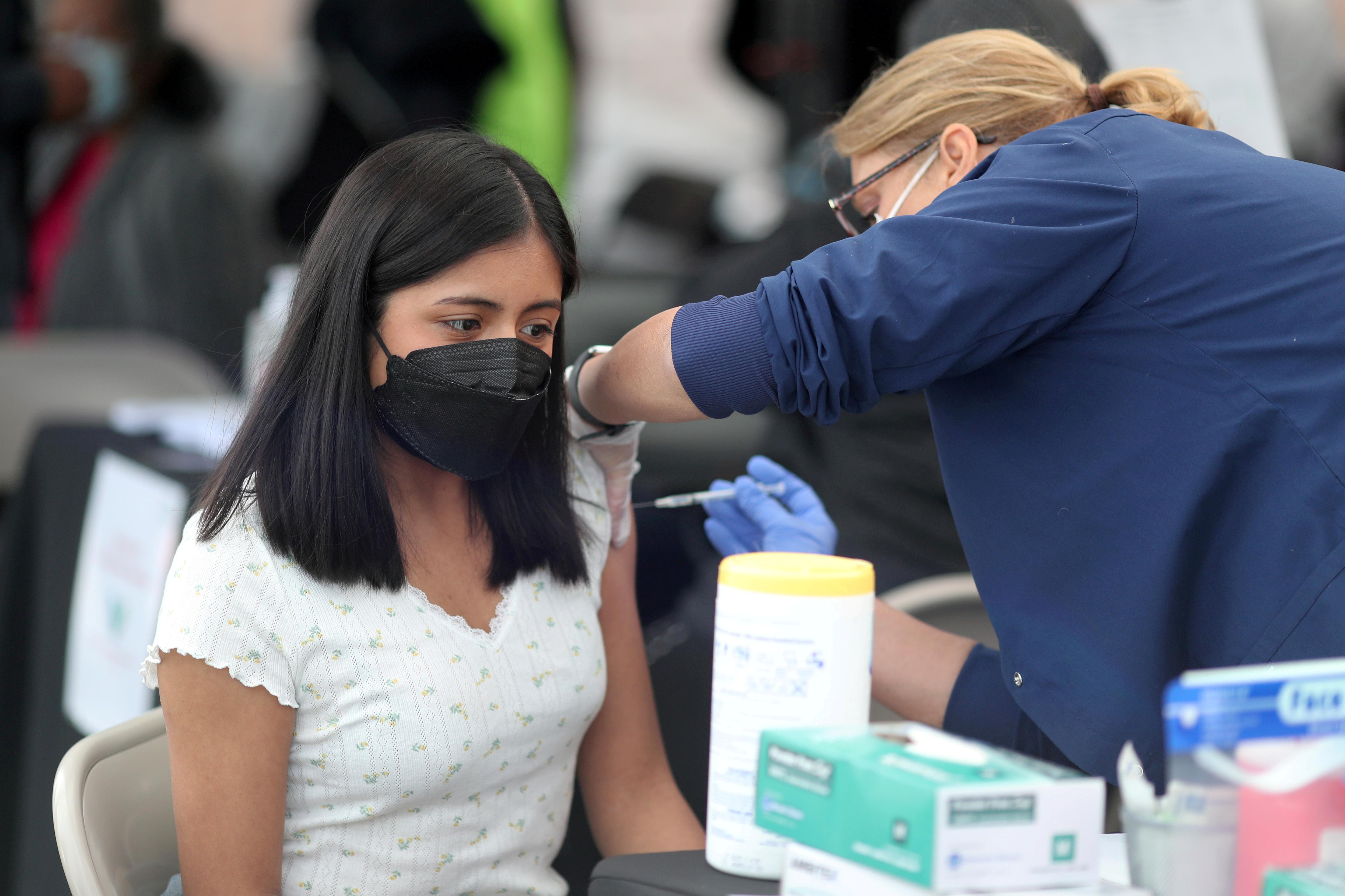 A woman receives a coronavirus disease (COVID-19) vaccination, at Jordan Downs in Los Angeles, California, U.S., March 10, 2021. REUTERS/Lucy Nicholson