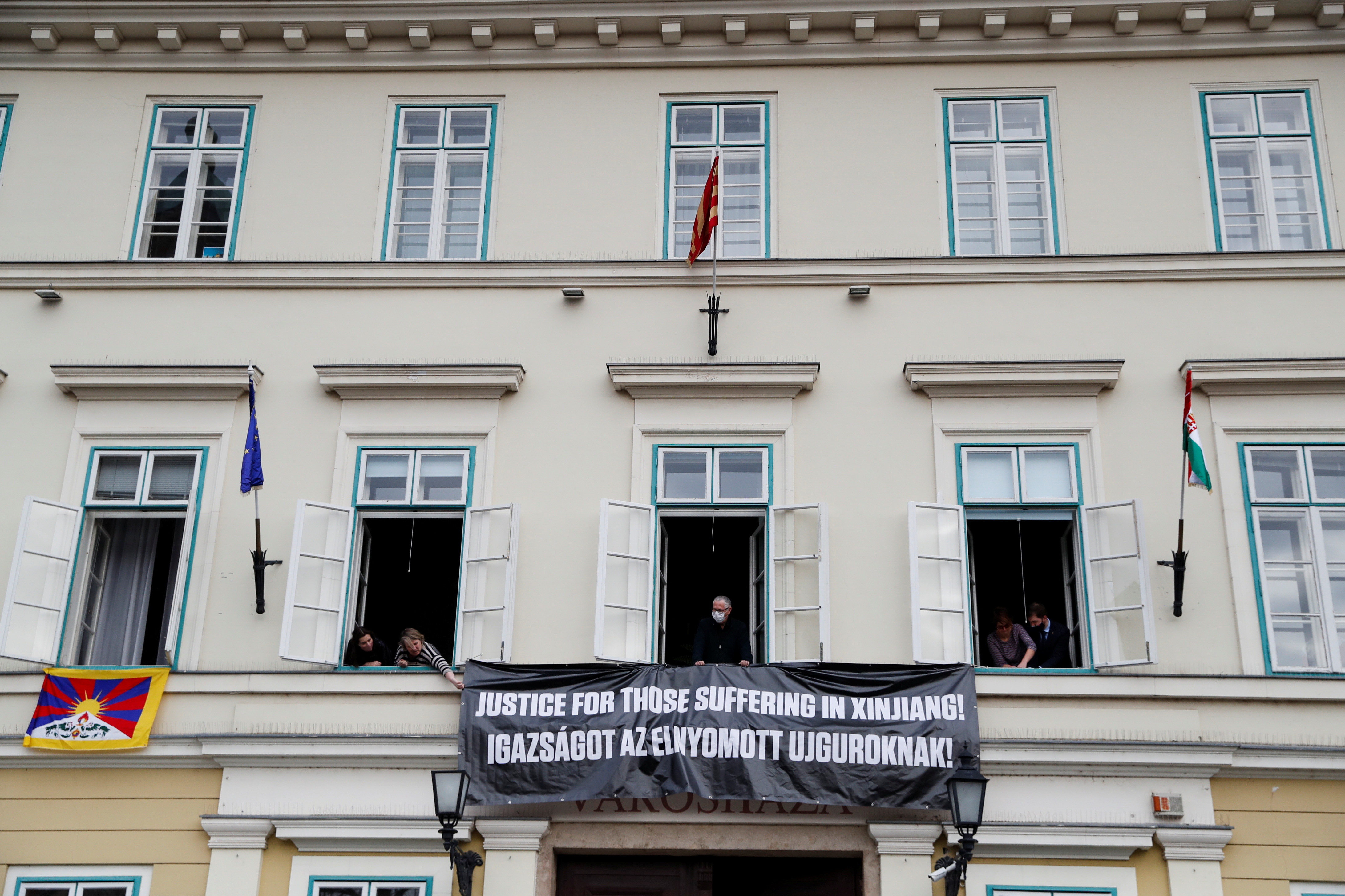 Hungarian opposition members hang a banner outside the District Mayor's Office building during the visit of Chinese Defence Minister Wei Fenghe, to protest over China's treatment of Uighurs, in Budapest, Hungary, March 25, 2021. REUTERS/Bernadett Szabo