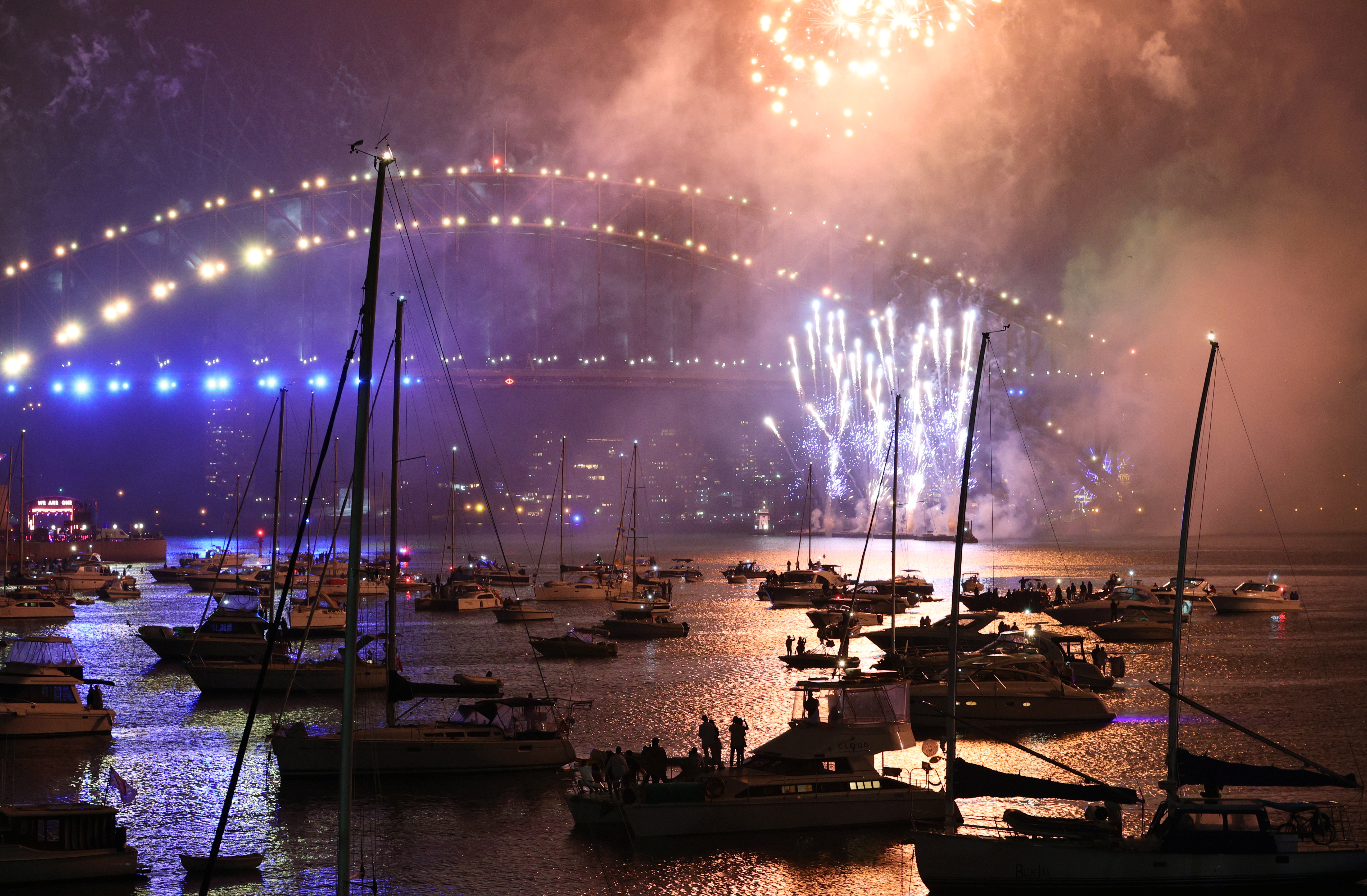 Fireworks explode over the boats and Sydney Harbour Bridge during downsized New Year's Eve celebrations due to an outbreak of the coronavirus disease (COVID-19) in Sydney, Australia, January 1, 2021. REUTERS/Loren Elliott
