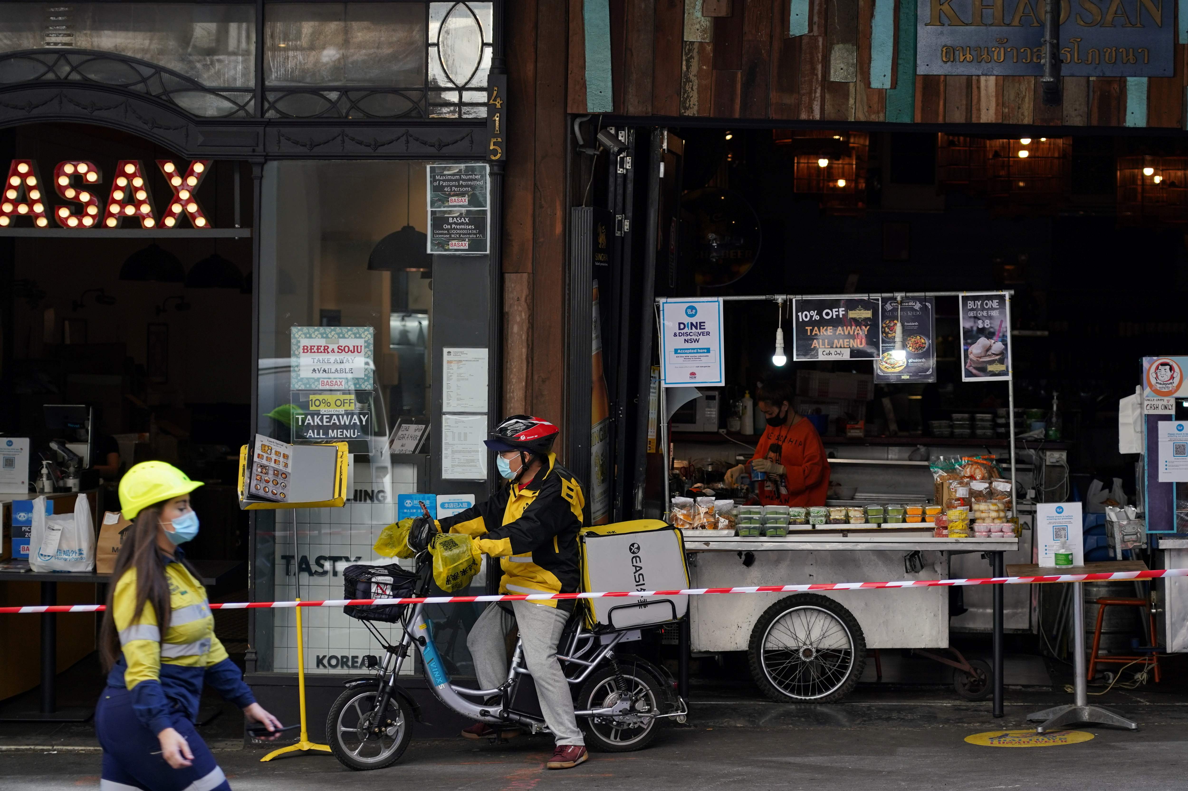 (From L) A construction worker, delivery courier and restaurant staff wear protective face masks while working in the city centre during a lockdown to curb the spread of a coronavirus disease (COVID-19) outbreak in Sydney, Australia, September 9, 2021.  REUTERS/Loren Elliott