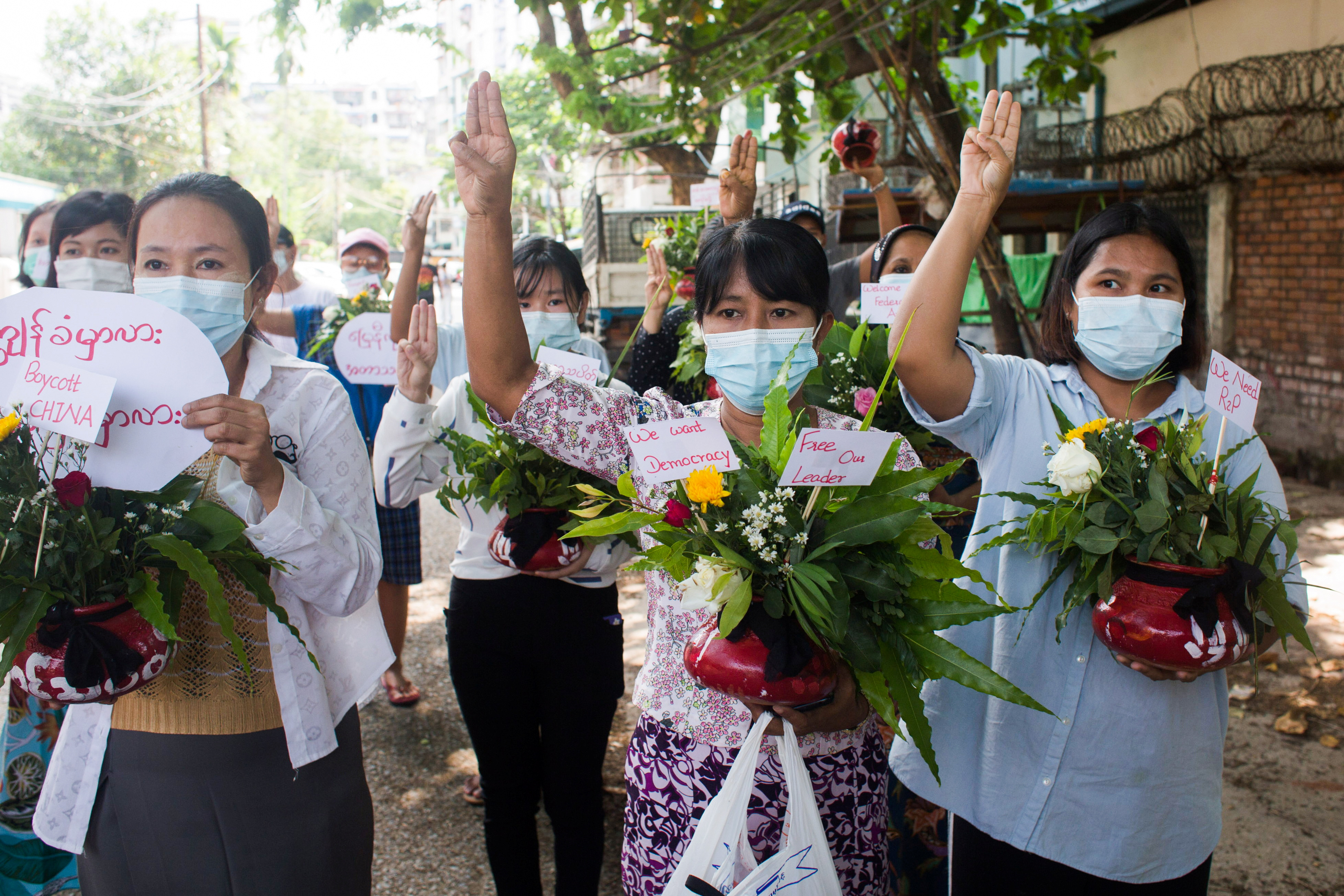 Women carry pots with flowers as they take part in a protest against the military coup in Yangon, Myanmar April 13, 2021. REUTERS/Stringer