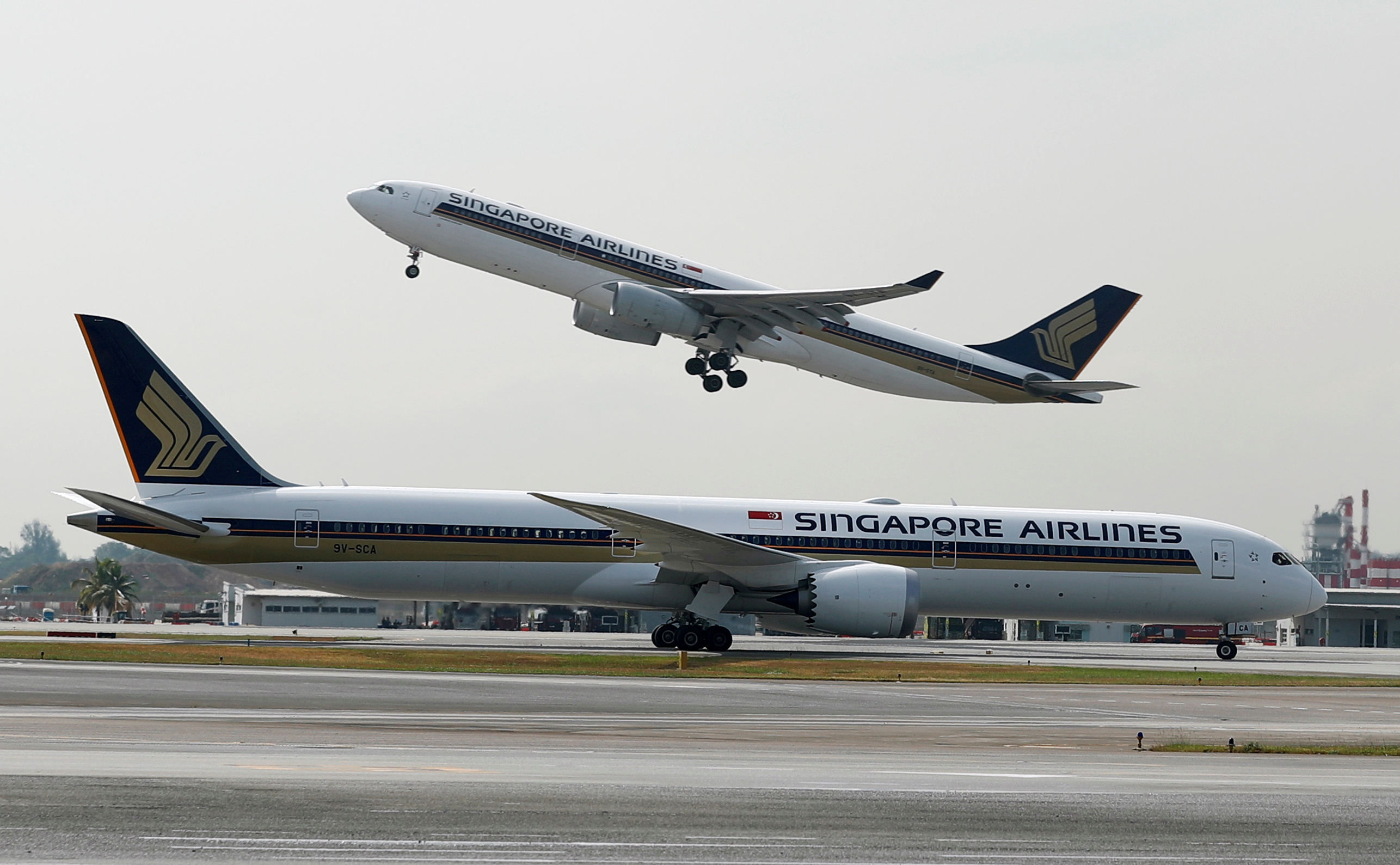 A Singapore Airlines Airbus A330-300 plane takes off behind a Boeing 787-10 Dreamliner at Changi Airport in Singapore March 28, 2018. REUTERS/Edgar Su/File Photo