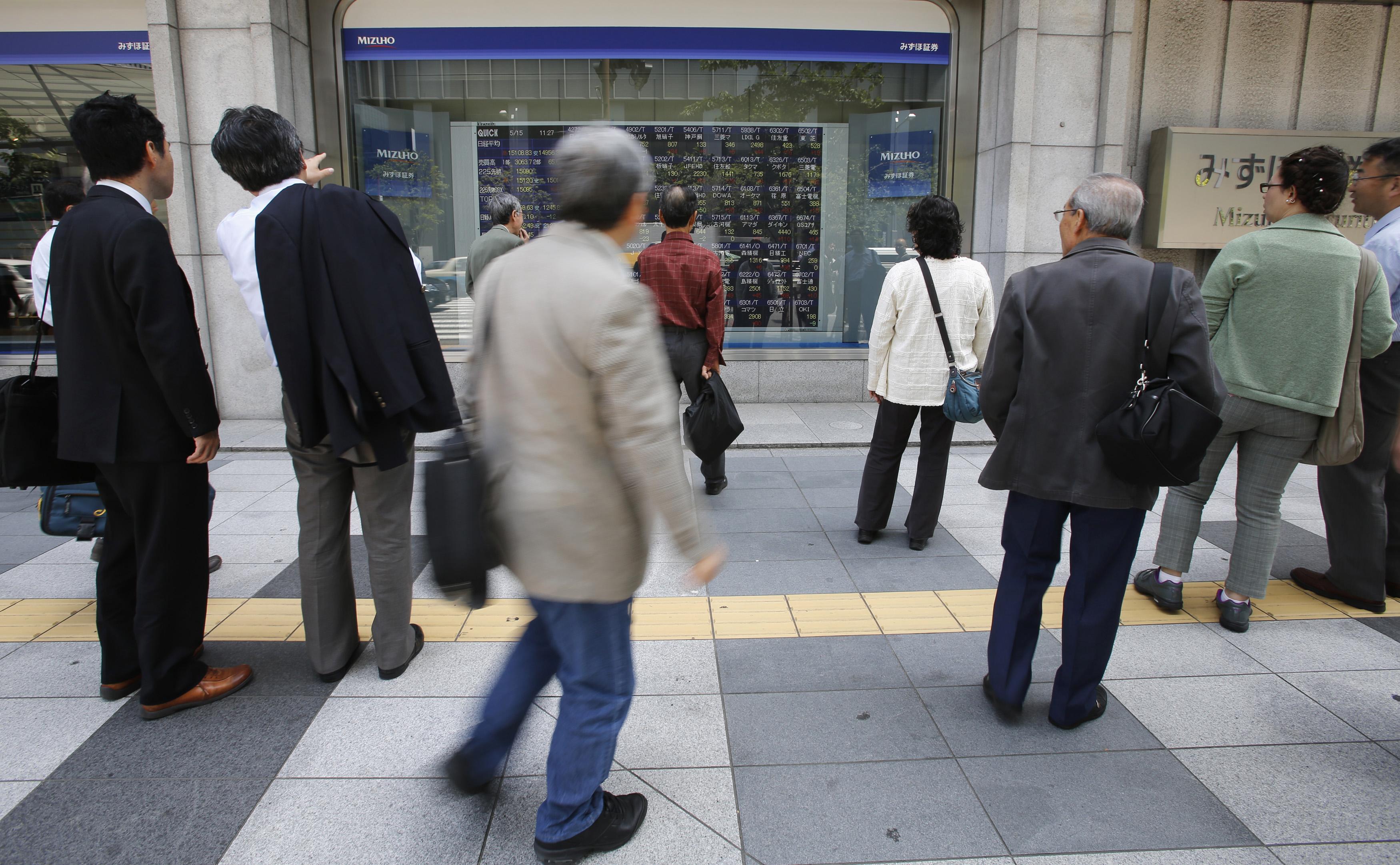 People look at a stock quotation board outside a brokerage in Tokyo May 15, 2013. REUTERS/Toru Hanai/Files