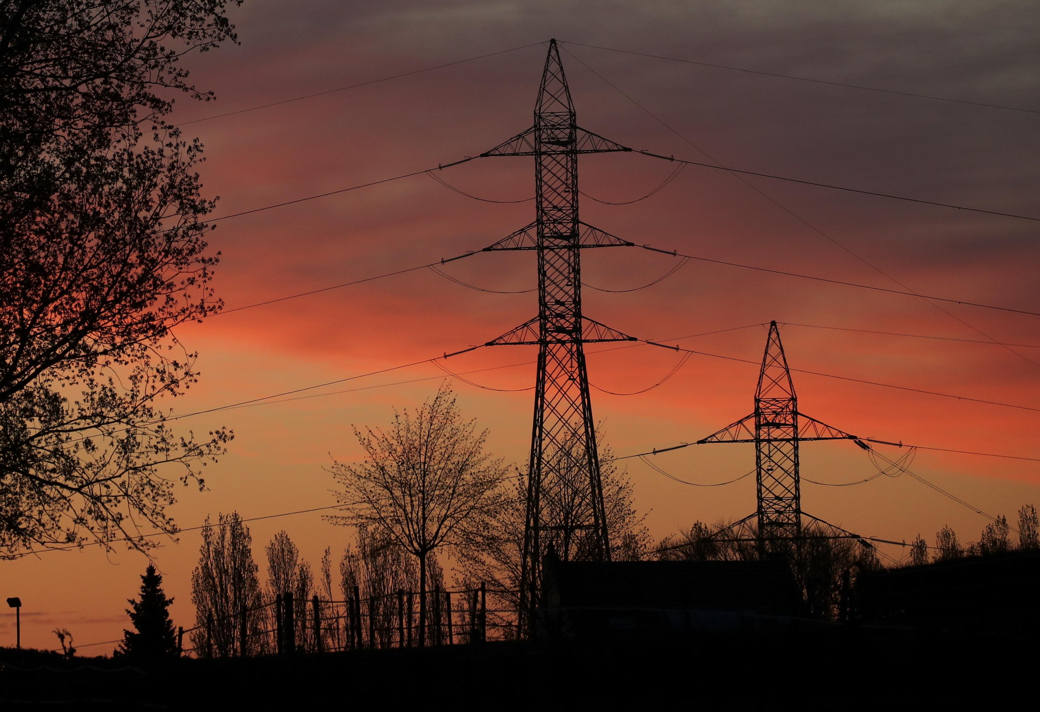 The sun rises behind electric pylons in Halle, Belgium April 27, 2021. REUTERS/Yves Herman