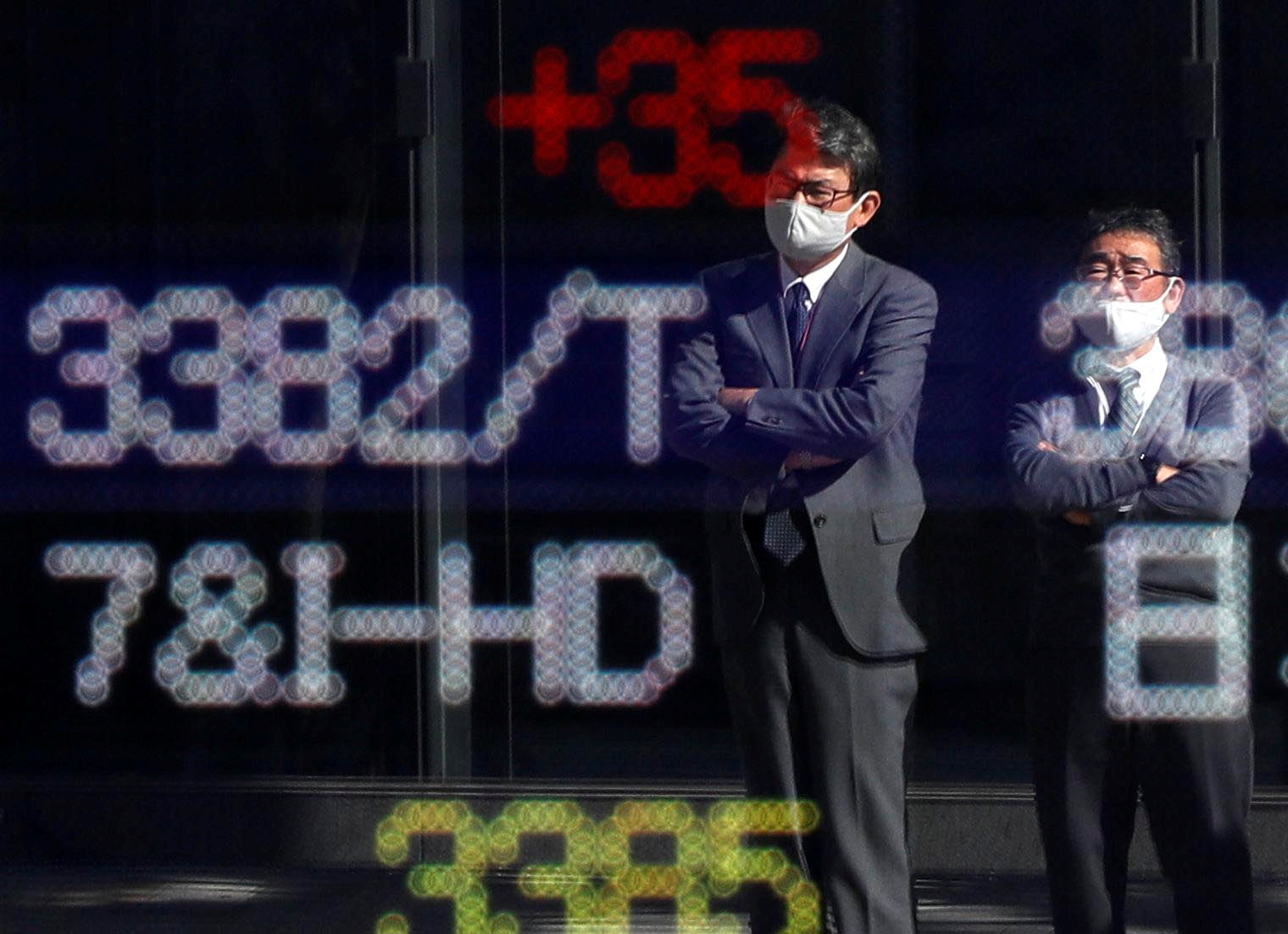 Passersby wearing protective face masks are reflected on a stock quotation board outside a brokerage, amid the coronavirus disease (COVID-19) outbreak, in Tokyo, Japan November 10, 2020. REUTERS/Issei Kato