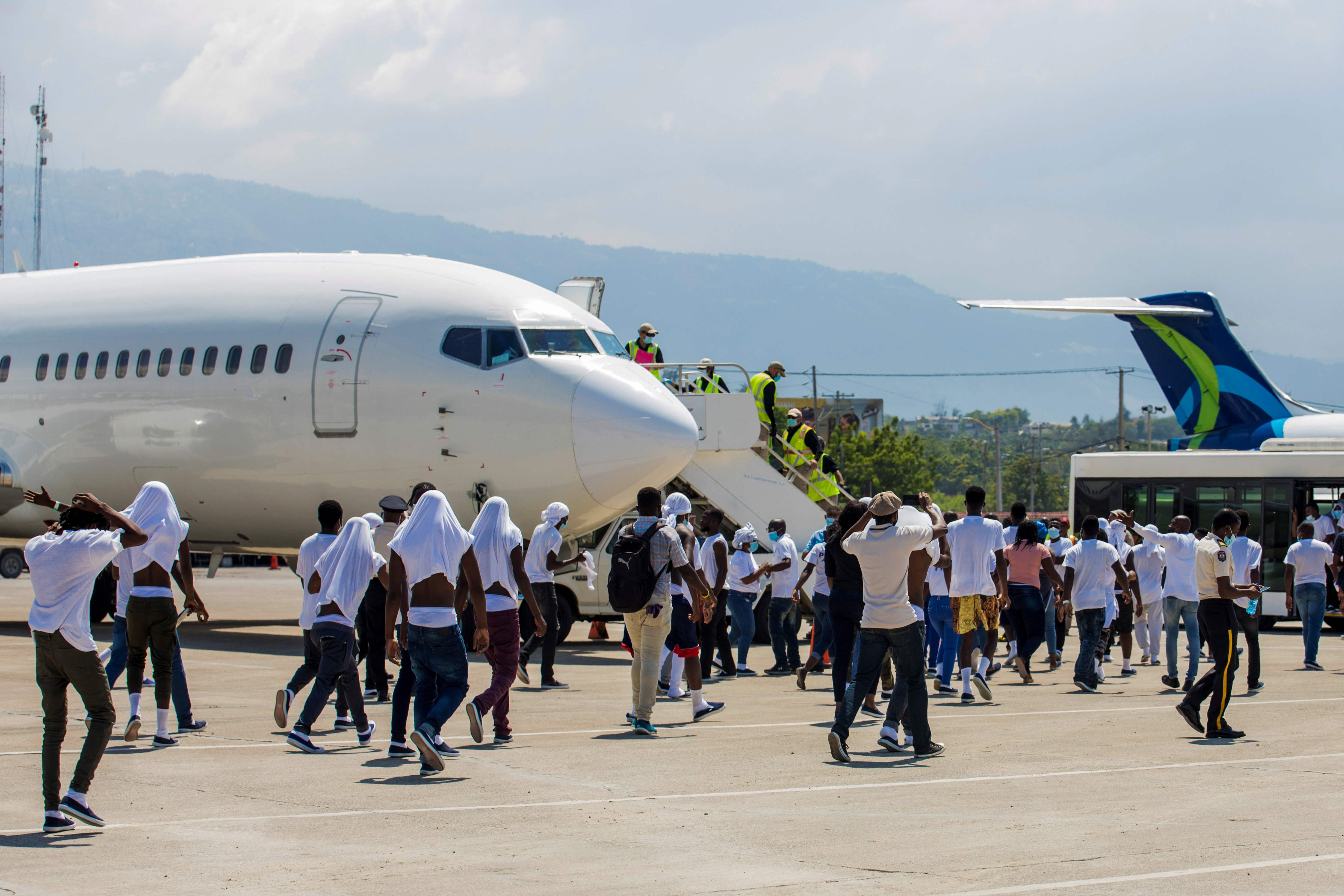 Haitian migrants board an airport bus aftter U.S. authorities flew them out of a Texas border city after crossing the Rio Grande river from Mexico, at Toussaint Louverture International Airport in Port-au-Prince, Haiti September 21, 2021. REUTERS/Ralph Tedy Erol