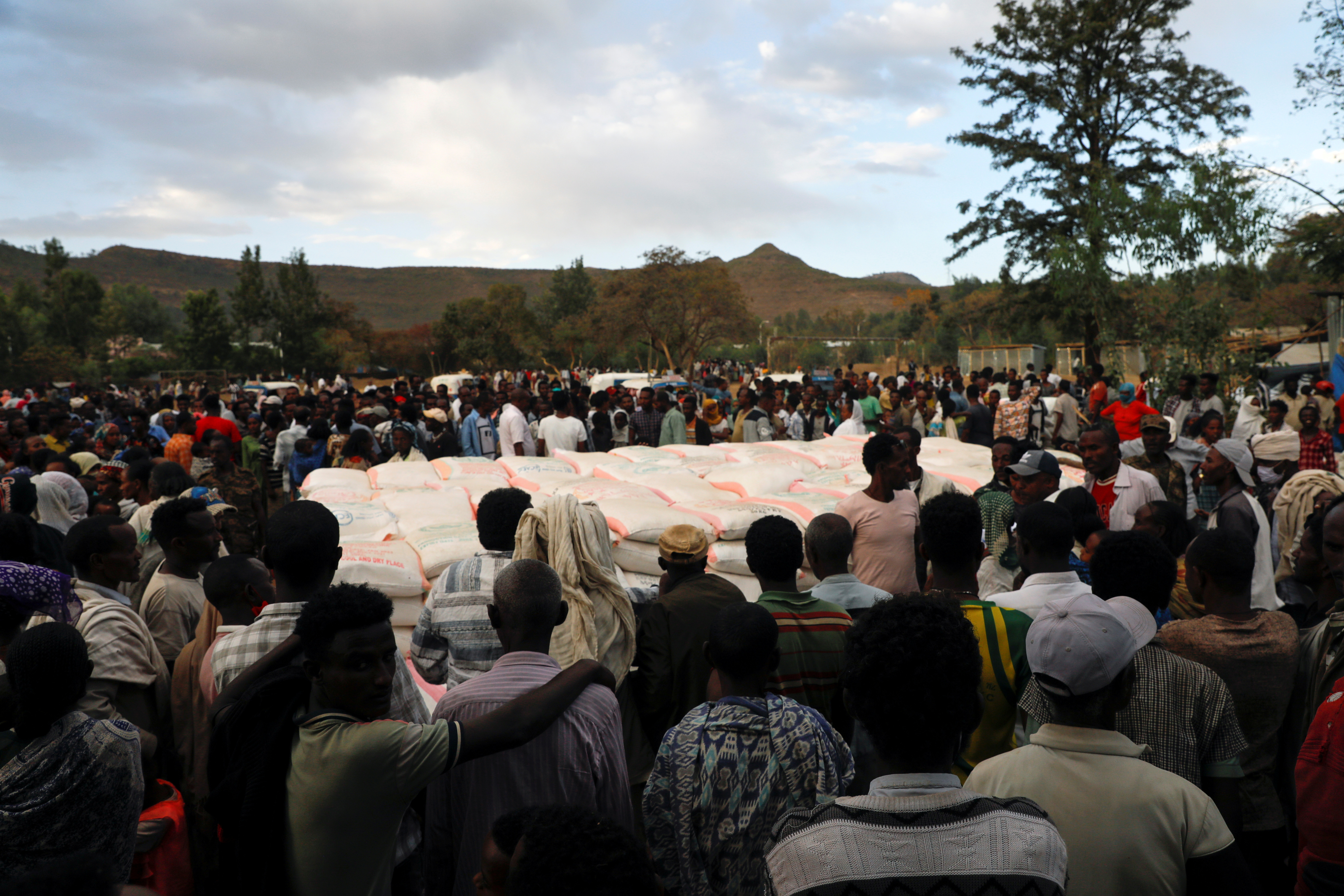 People stand in line to receive food donations, at the Tsehaye primary school, which was turned into a temporary shelter for people displaced by conflict, in the town of Shire, Tigray region, Ethiopia, March 15, 2021. Picture taken March 15, 2021.    REUTERS/Baz Ratner/File Photo