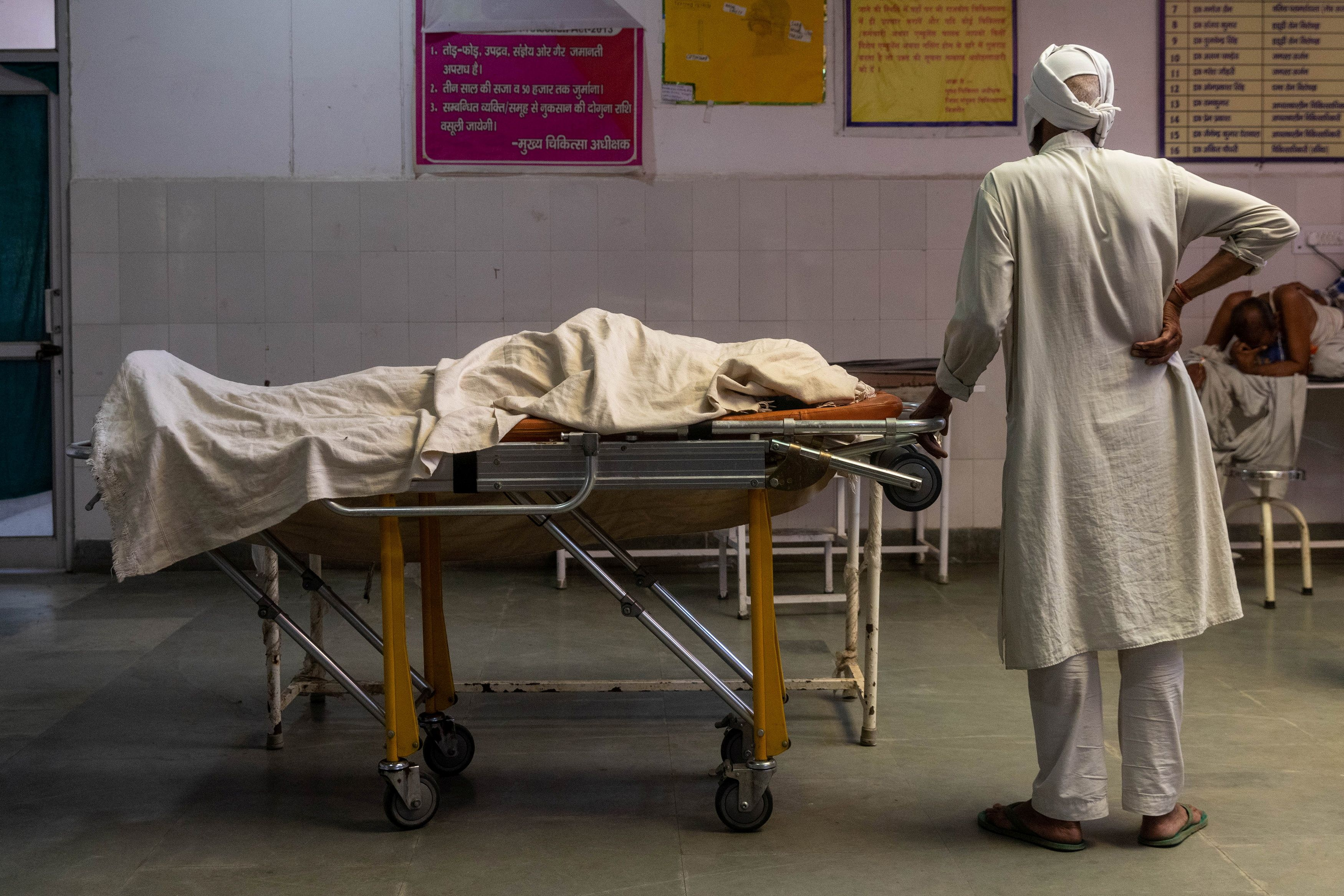 A man stands next to the body of his wife, who died due to breathing difficulties, inside an emergency ward of a government-run hospital, amidst the coronavirus disease (COVID-19) pandemic, in Bijnor, Uttar Pradesh, India, May 11, 2021. REUTERS/Danish Siddiqui