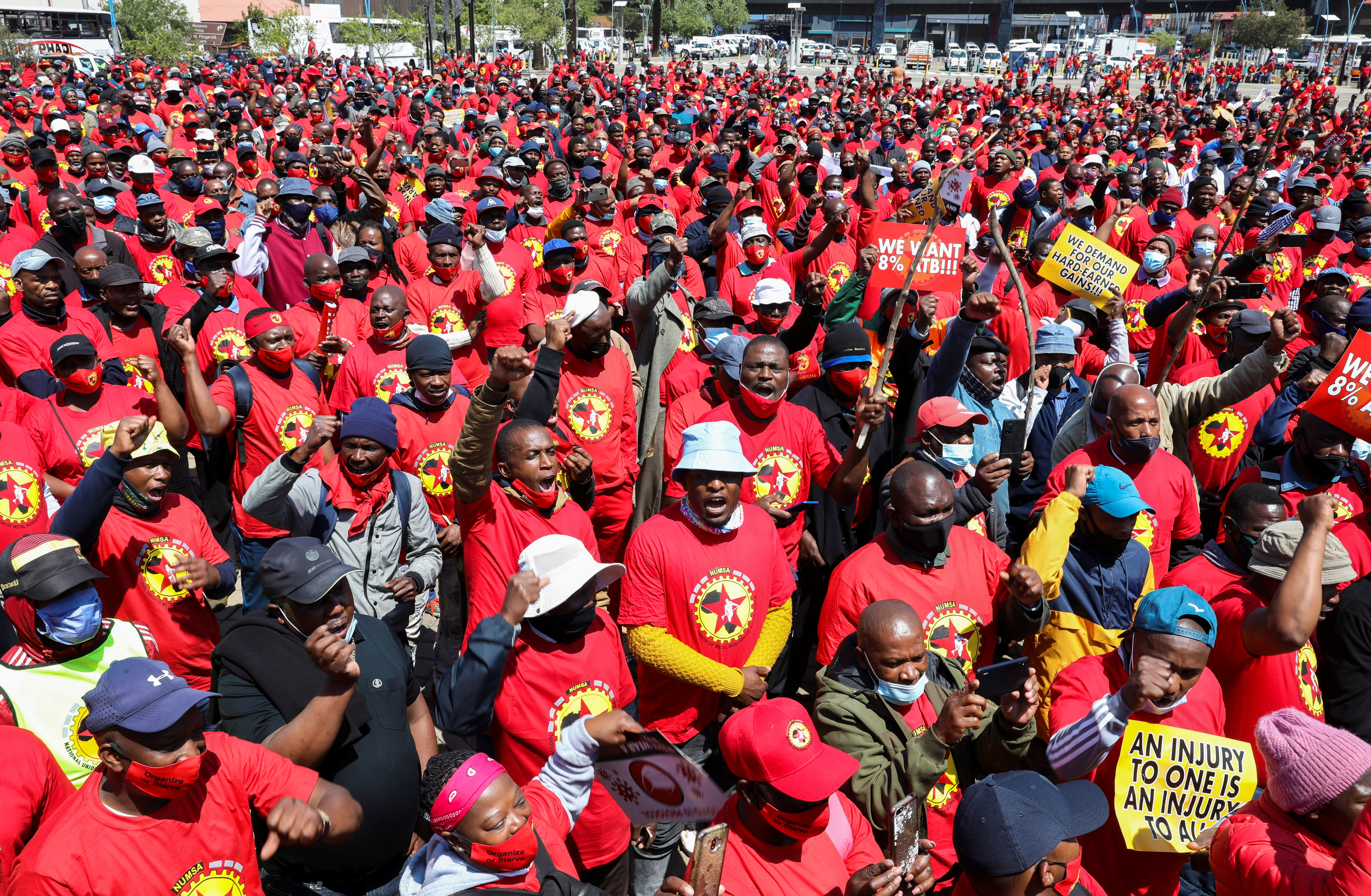 Members of the National Union of Metalworkers of South Africa (NUMSA) hold placards as they gather ahead of an indefinite strike, threatening to choke supplies of parts to make new cars and accessories, in Johannesburg, South Africa, October 5, 2021. REUTERS/Siphiwe Sibeko