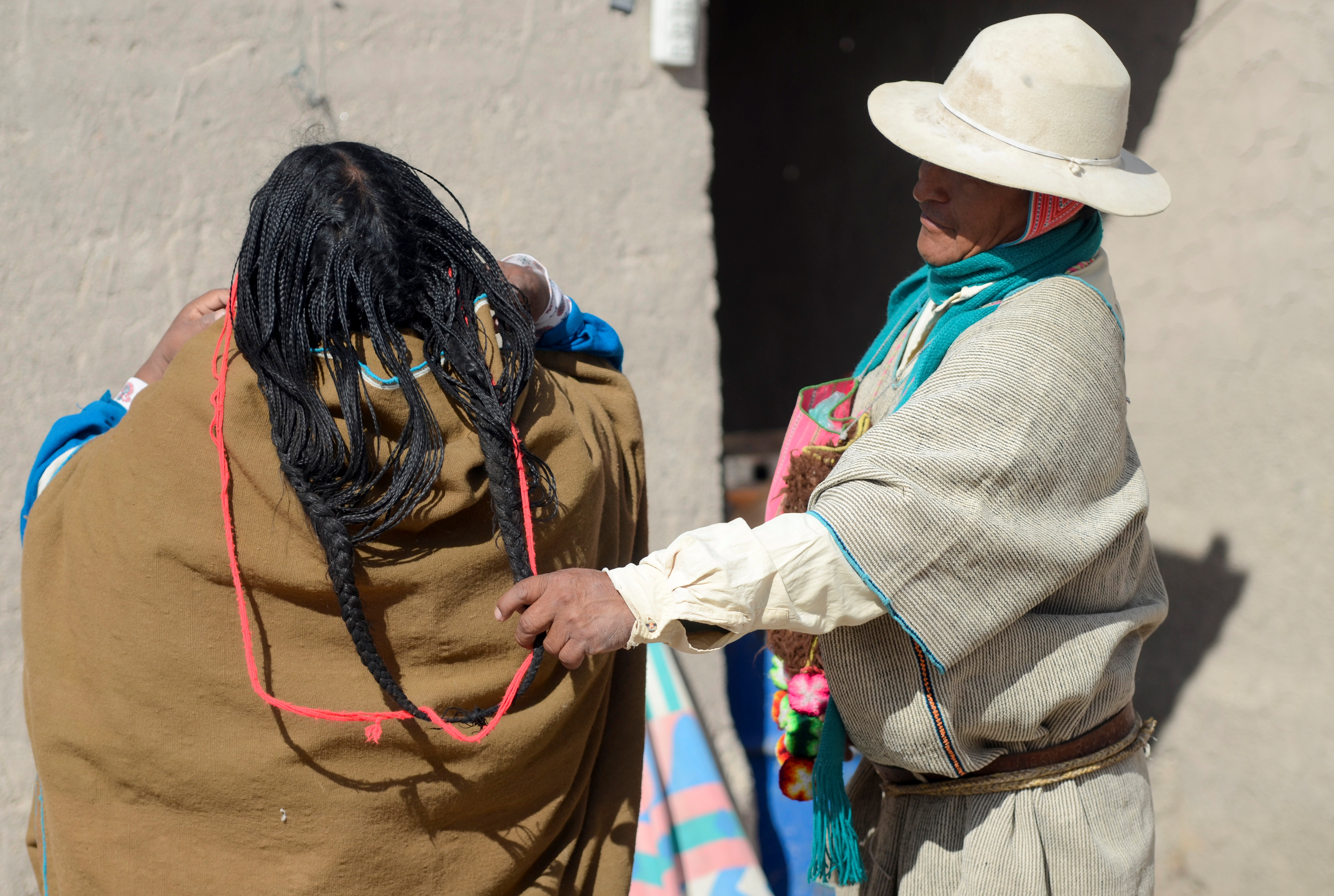 Fausto Lopez helps his wife Petronila Mollo with her hair before going to the main square to be vaccinated against the coronavirus disease (COVID-19) along with others, in Uru Chipaya, Bolivia July 23, 2021. REUTERS/Claudia Morales