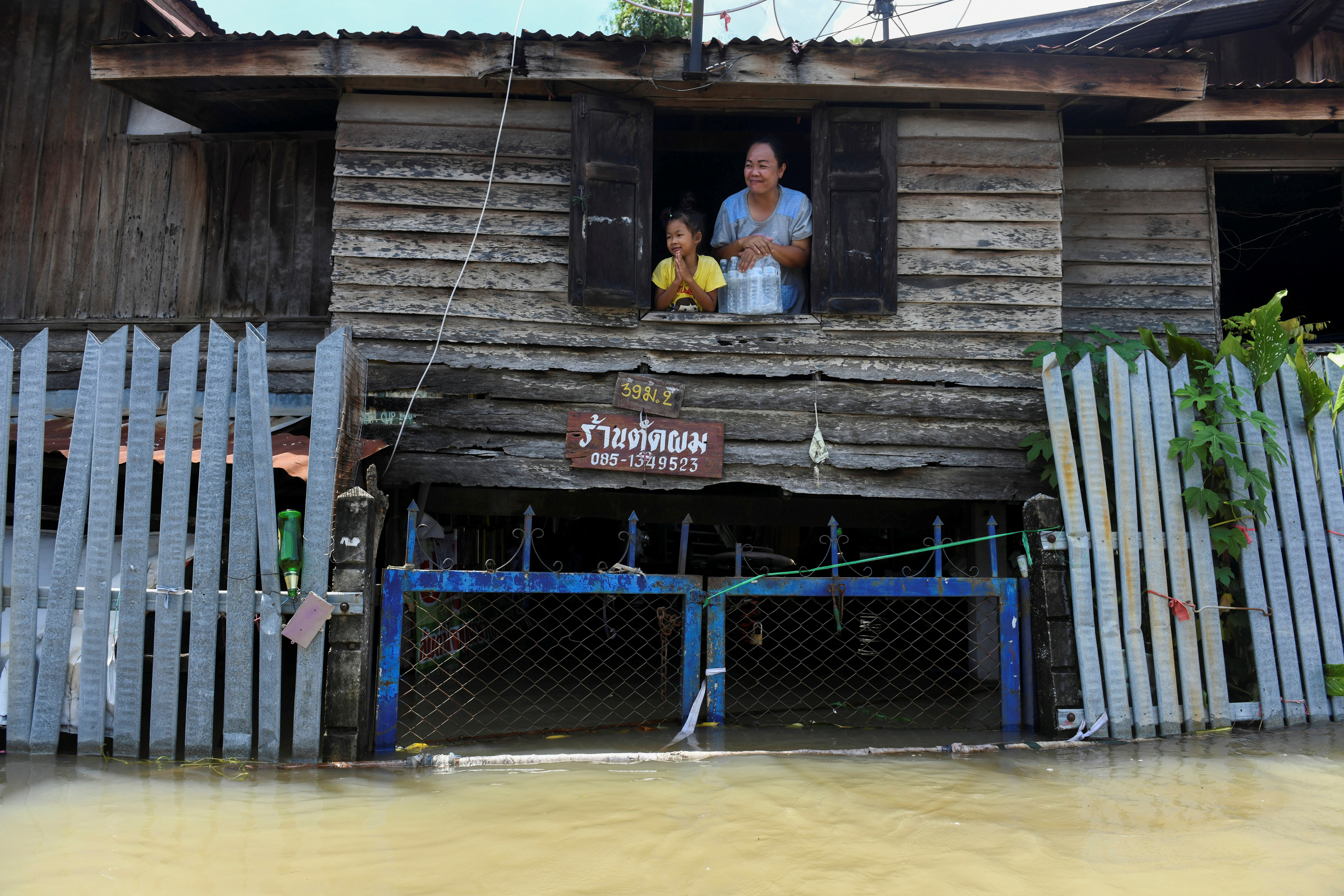 A mother and daughter are seen on the second floor of their house in a flooded area in Ban Sai village, Ban Mi district in Lopburi province, Thailand, September 30, 2021. REUTERS/Panumas Sanguanwong