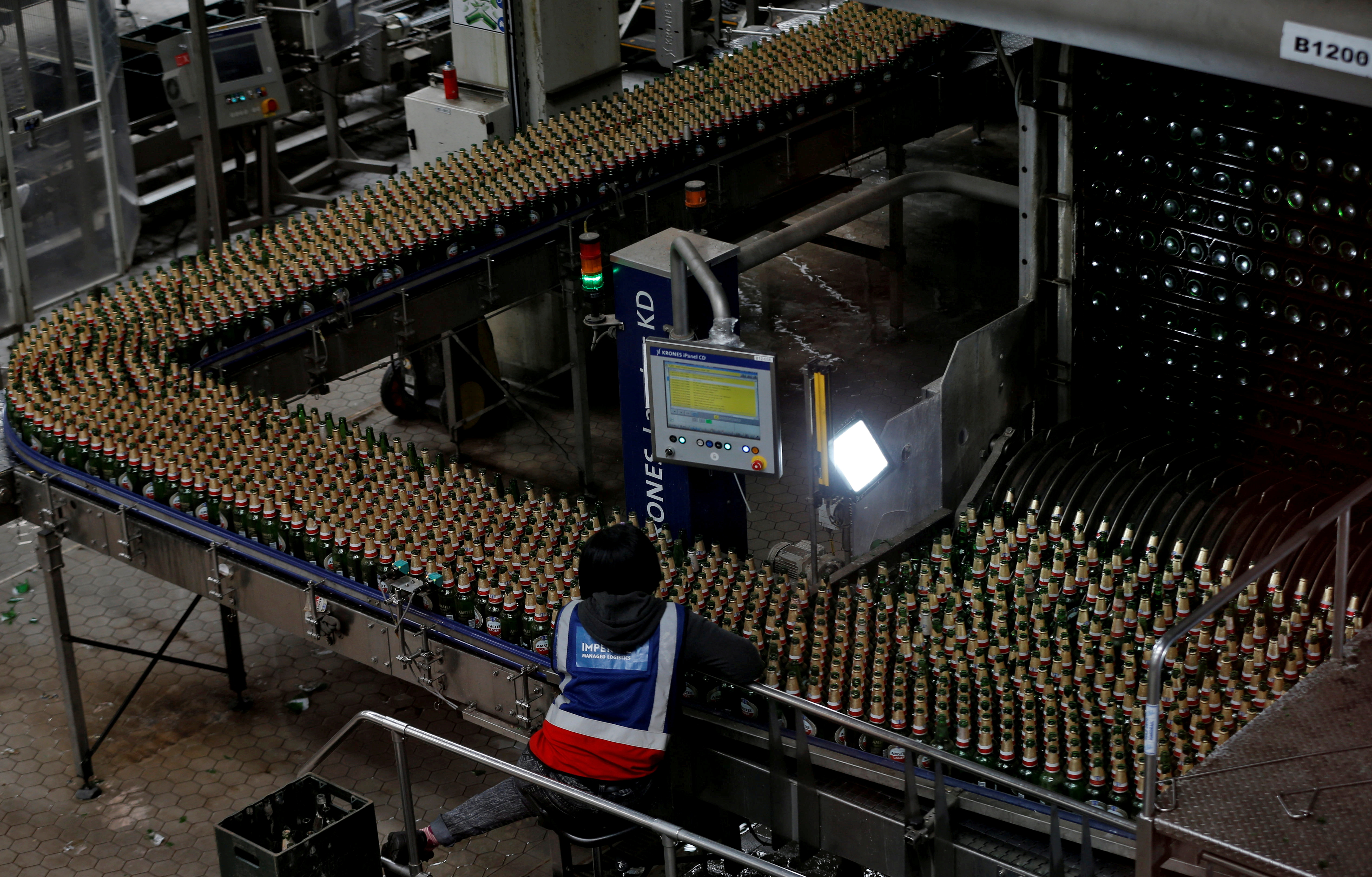 A worker inspects beer bottles on a conveyor belt at the Sedibeng Brewery in Midvaal outside Johannesburg, South Africa, September 15, 2016. REUTERS/Siphiwe Sibeko/File Photo