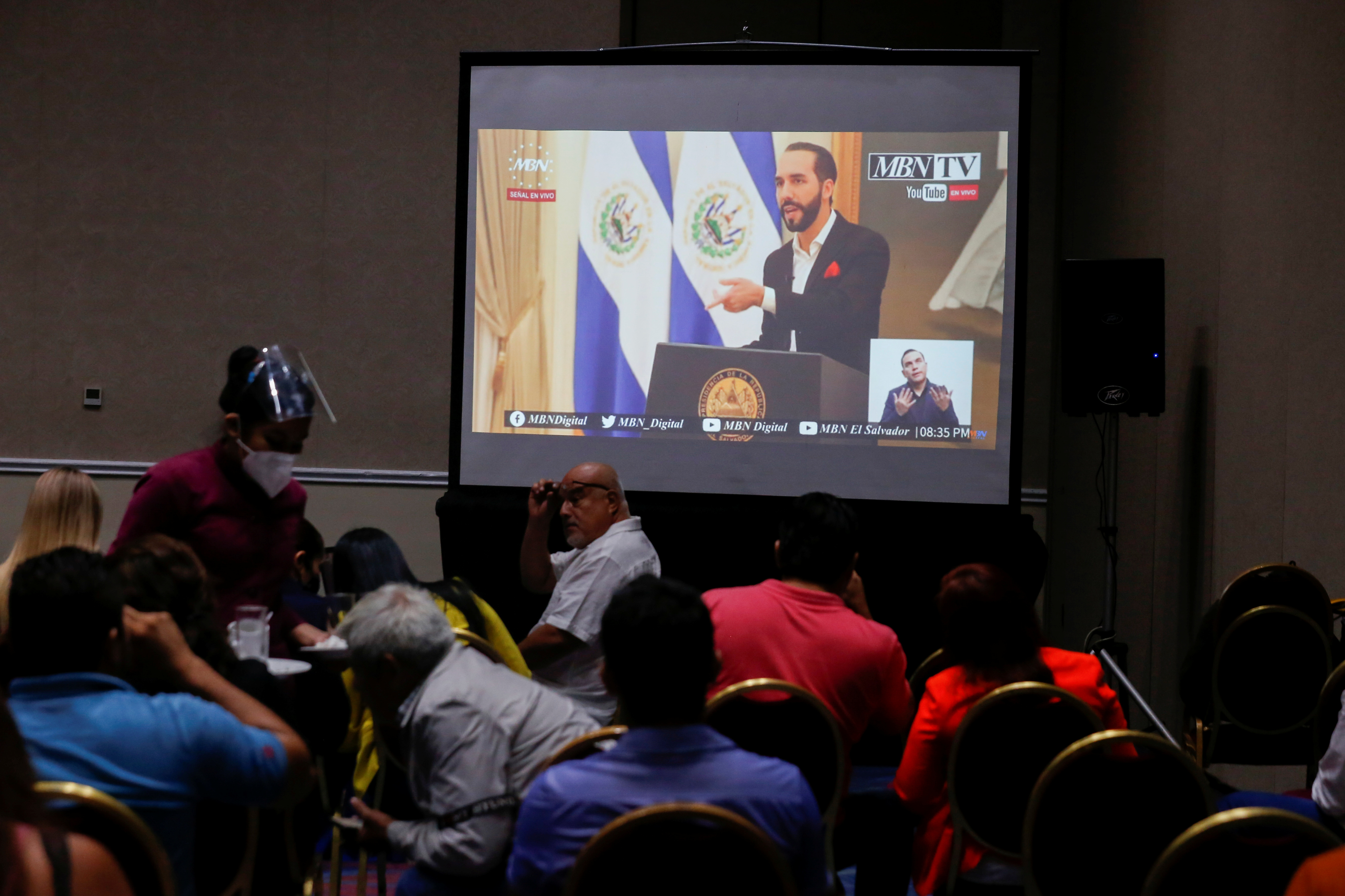 People watch El Salvador President Nayib Bukele on an online transmission during a Bitcoin investment event, in San Salvador, El Salvador June 24, 2021. REUTERS/Jose Cabezas