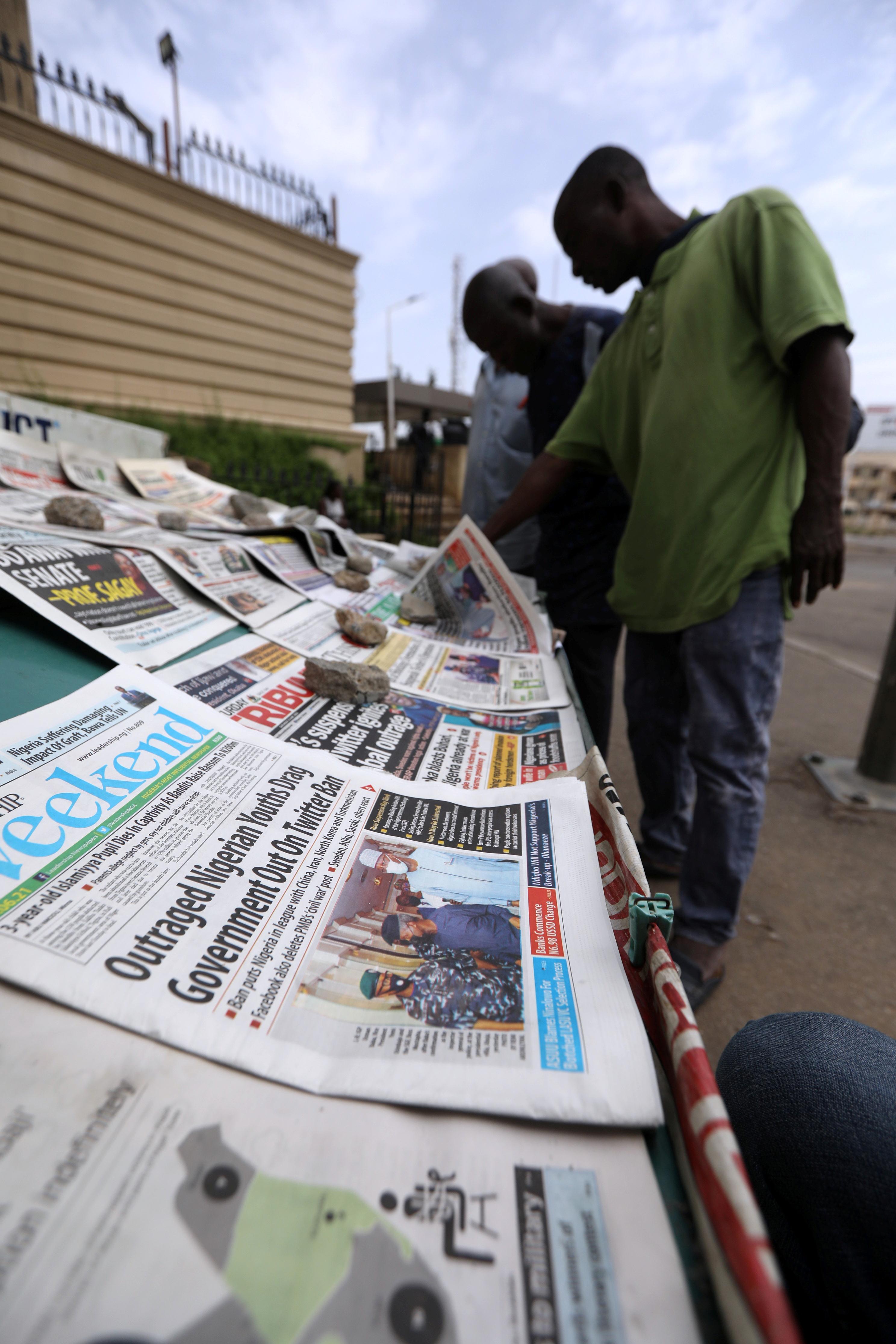 Pedestrians look at newspapers in Abuja, Nigeria June 5, 2021. REUTERS/Afolabi Sotunde