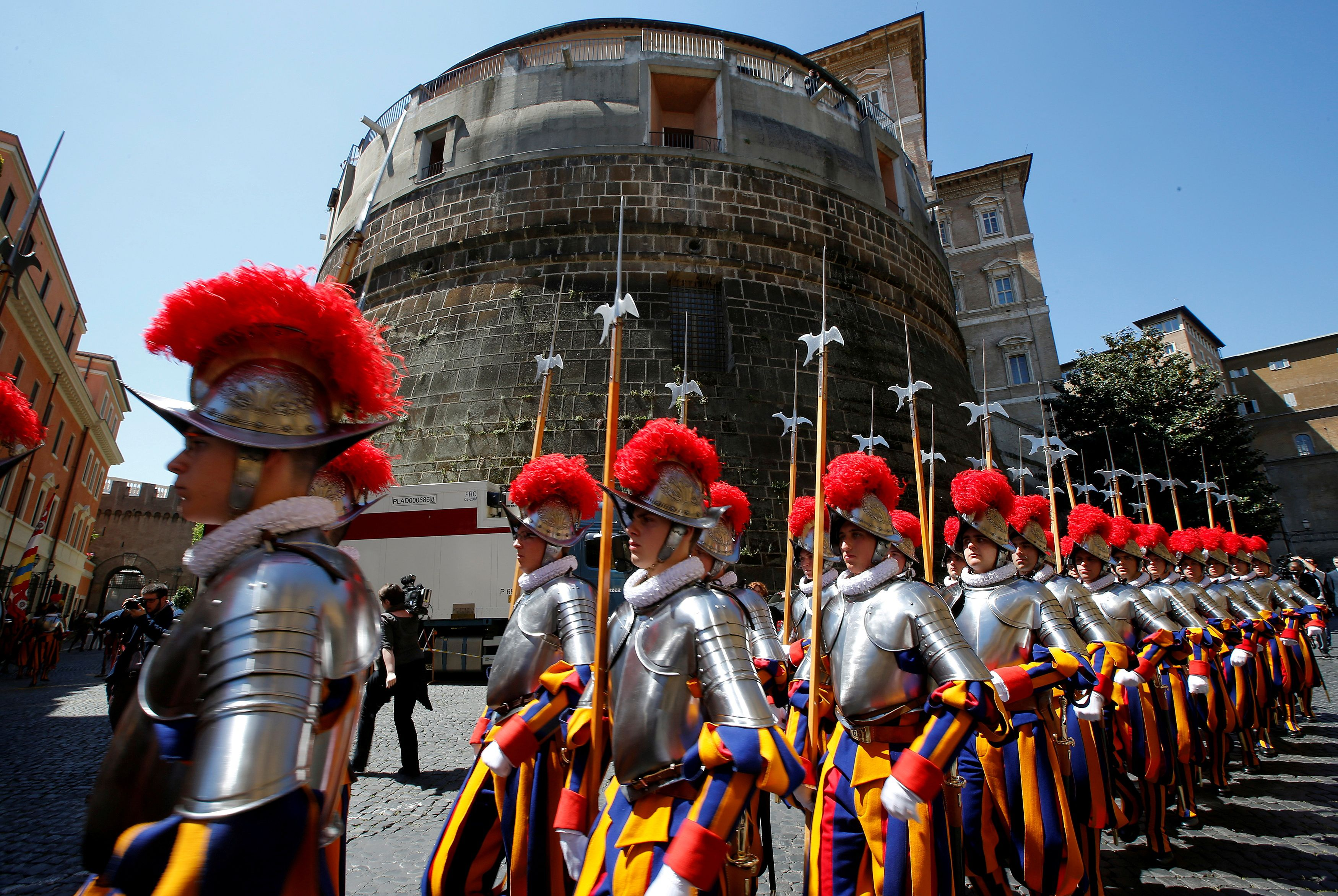 New recruits of the Vatican's elite Swiss Guard march in front of the tower of the Institute for Works of Religion (IOR) during the swearing-in ceremony at the Vatican May 6, 2014. REUTERS/Tony Gentile