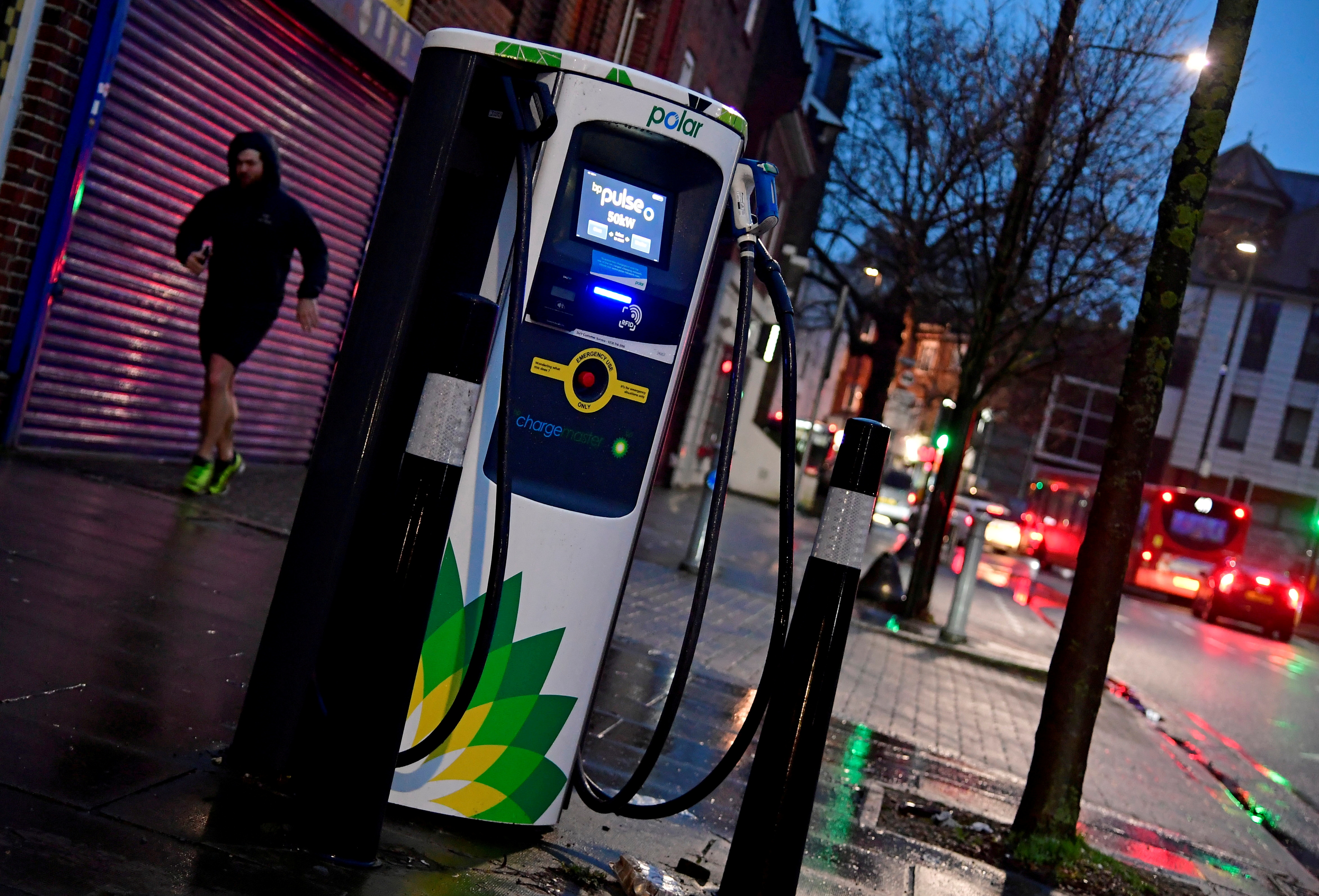 A man runs past a BP (British Petroleum) EV (Electric Vehicle) charge point in London, Britain, January 30, 2021. REUTERS/Toby Melville