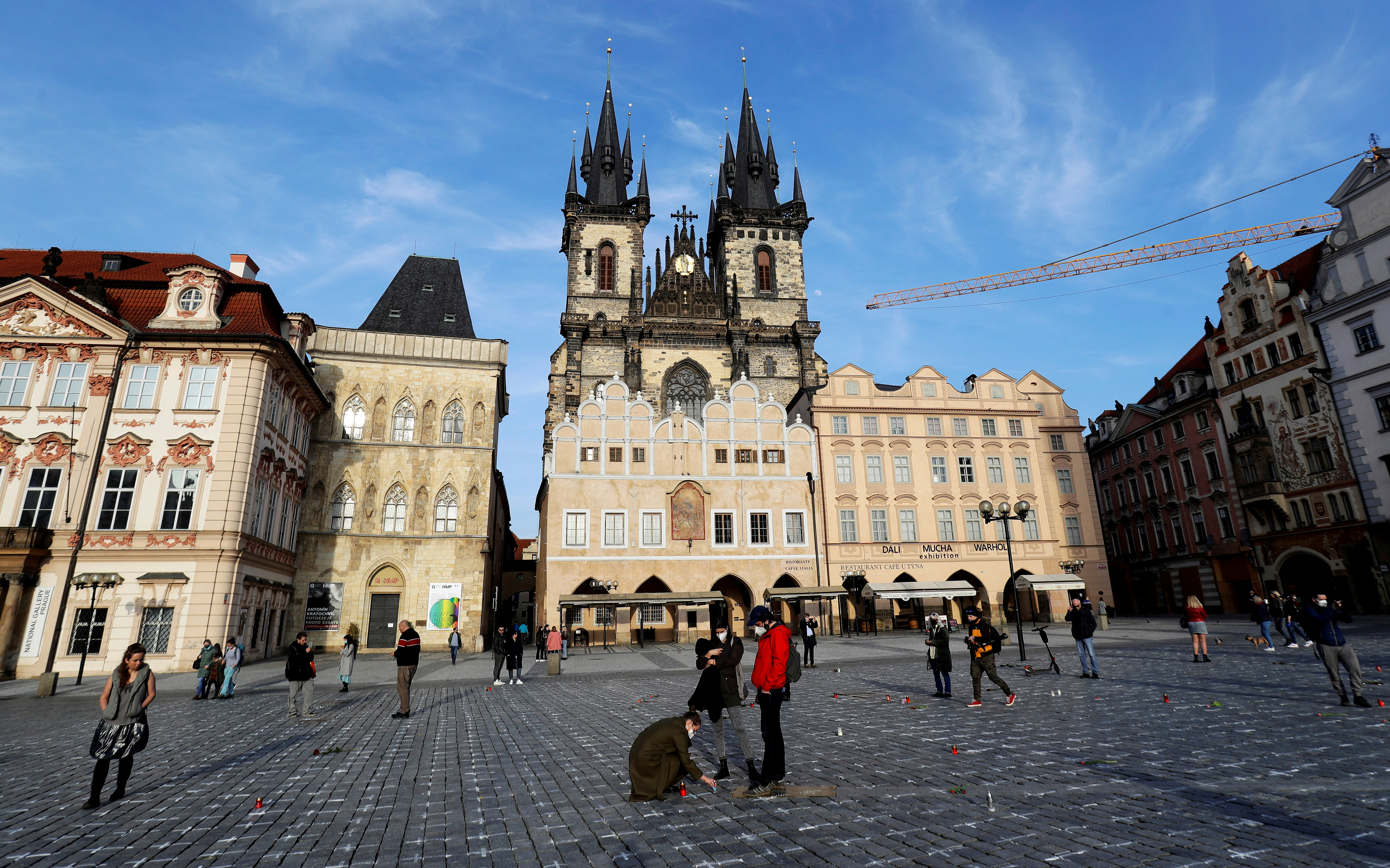 People pay their respects at the Old Town Square where thousands of crosses have been painted on a pavement to commemorate the first anniversary since the death of the first Czech coronavirus disease (COVID-19) patient in Prague, Czech Republic, March 25, 2021. REUTERS/David W Cerny/File Photo