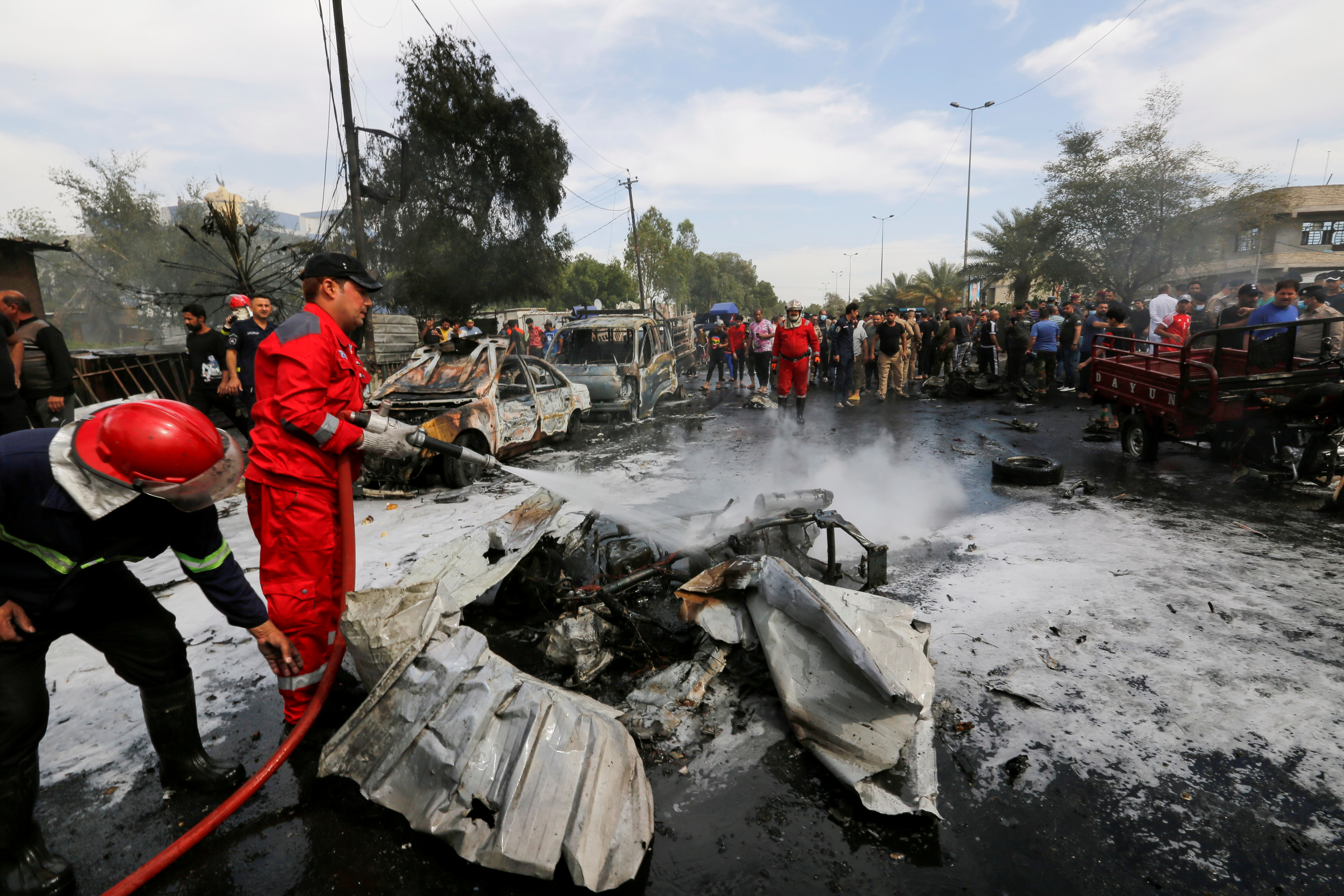Firefighters inspect the site of a car bomb attack in Sadr City district of Baghdad, Iraq April 15, 2021. REUTERS/Wissam al-Okili