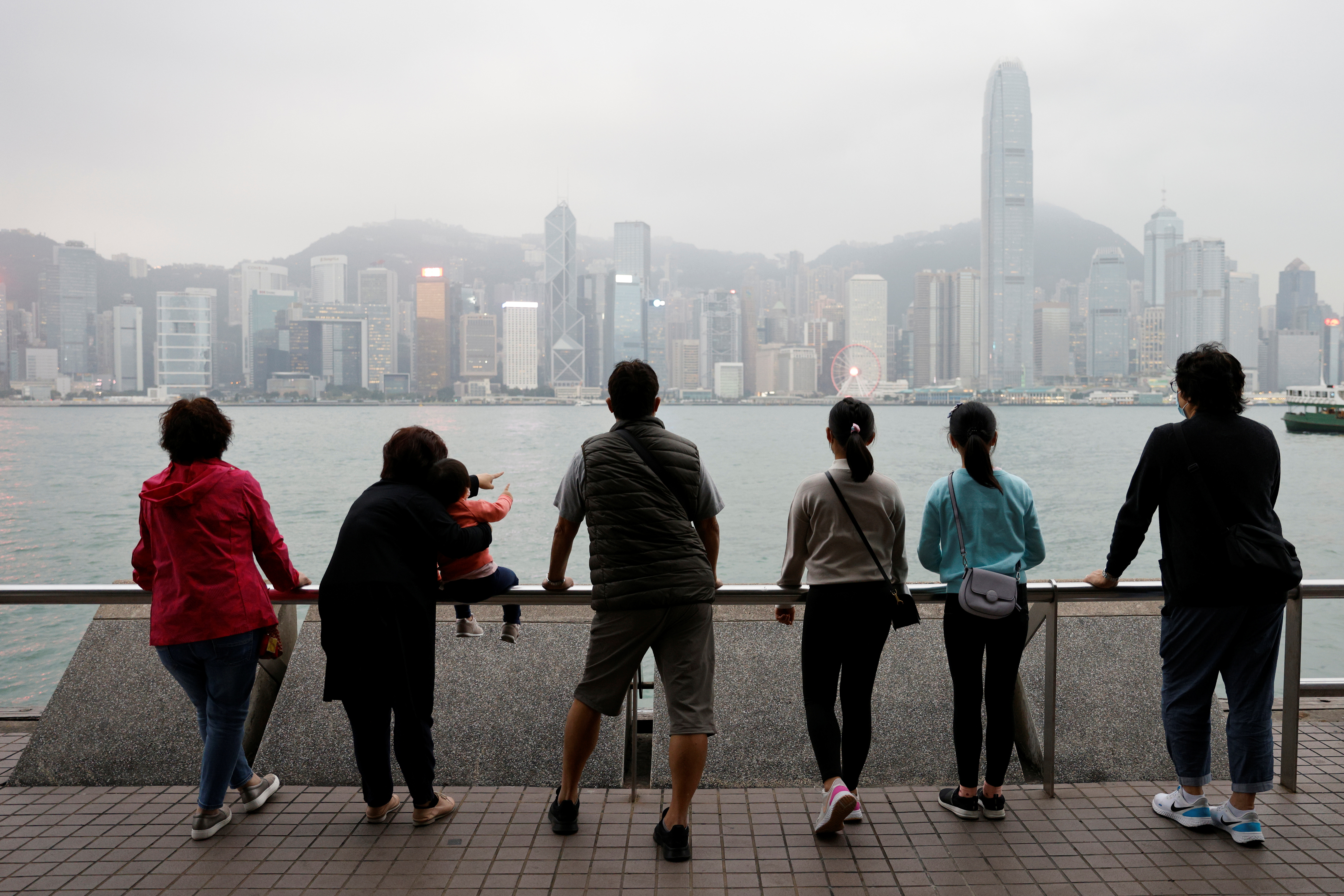 The Lai family, who are emigrating to Scotland, look out over the city's skyline on an outing to Tsim Sha Tsui in Hong Kong, China, December 14, 2020. REUTERS/Tyrone Siu