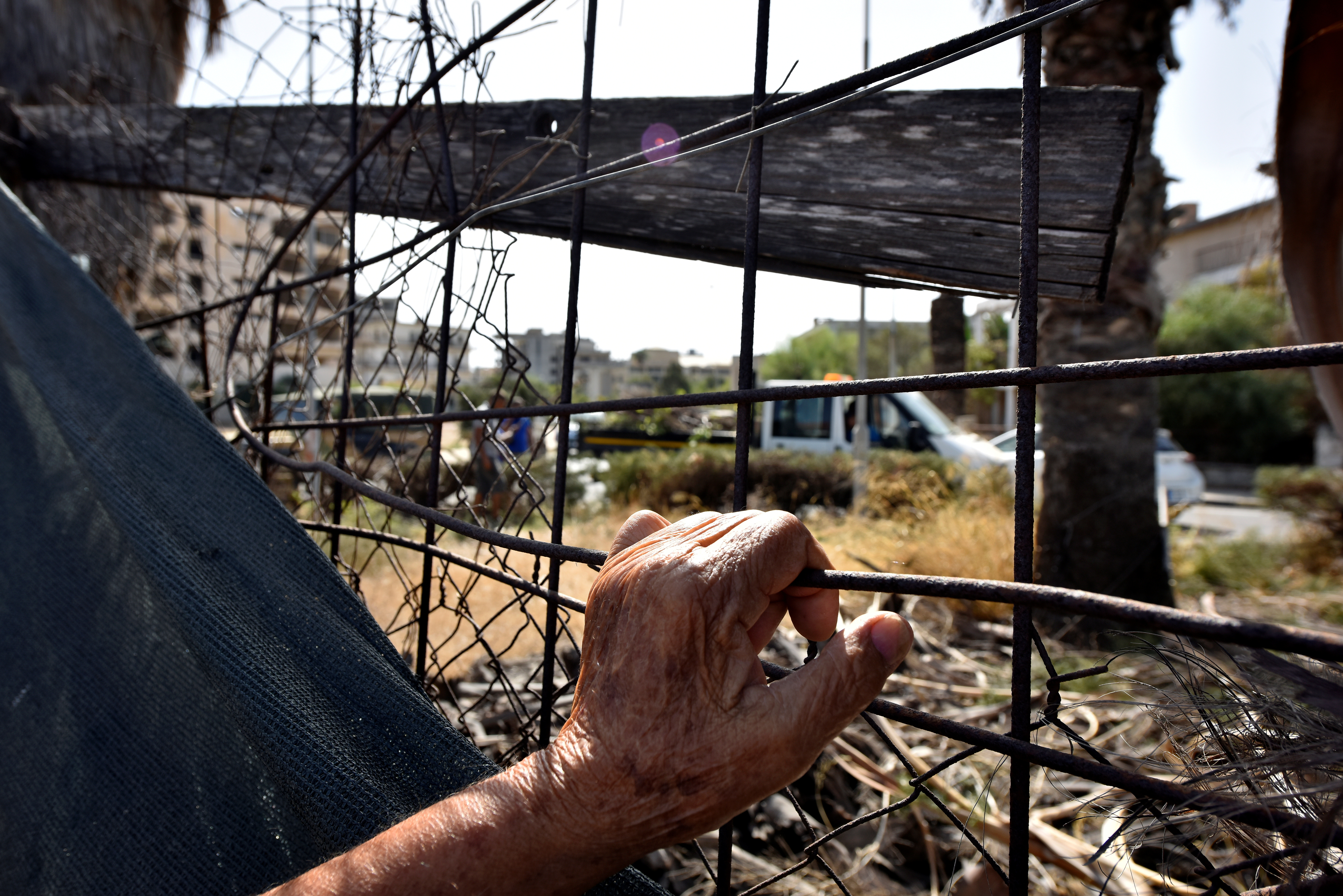 A man holds a fence in an area fenced off by the Turkish military since 1974 in the abandoned coastal area of Varosha, a suburb of the town of Famagusta in Turkish-controlled northern Cyprus, October 8, 2020. REUTERS/Harun Ucar/File Photo