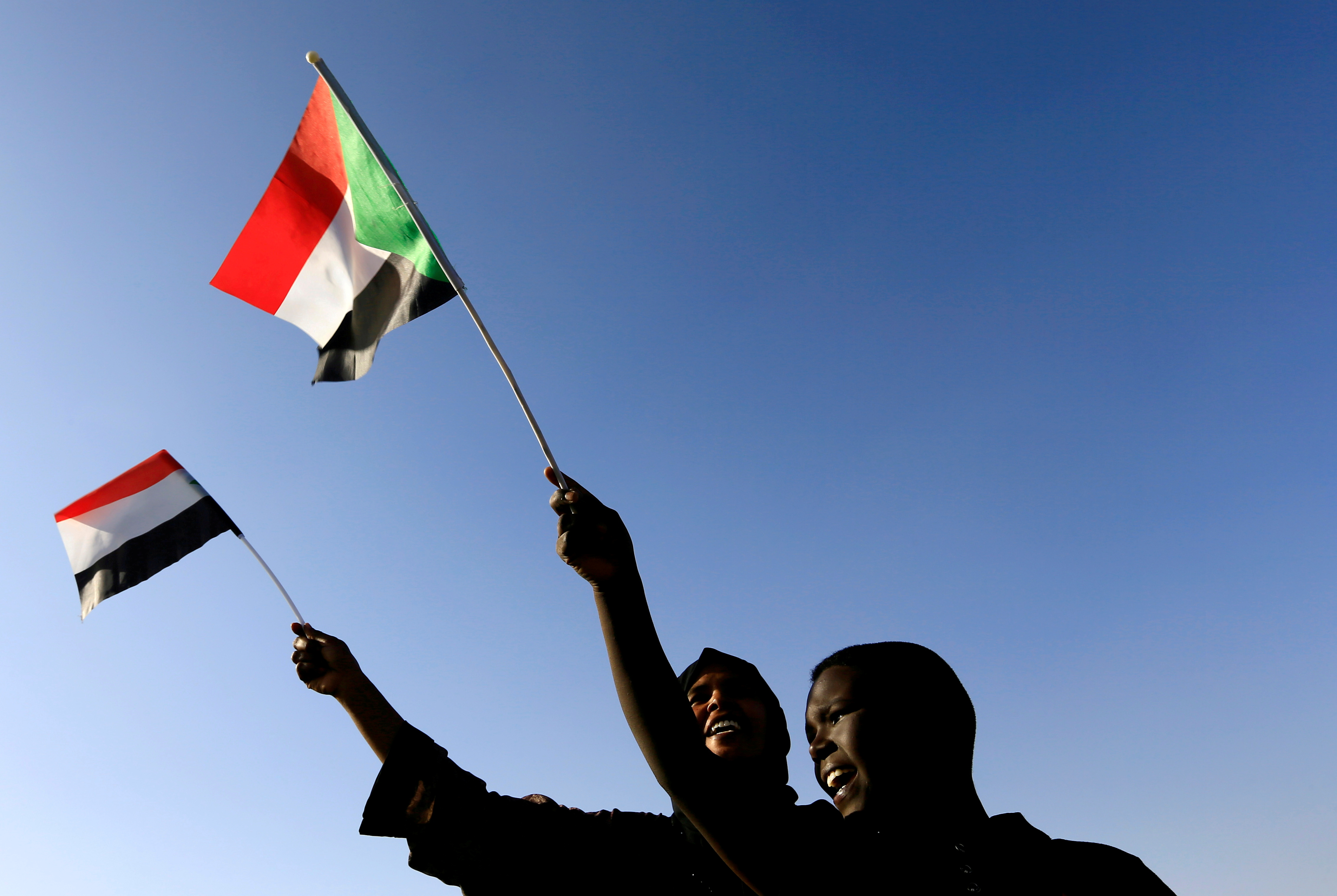 Sudanese civilians wave their national flag as they gather at the freedom square during the first anniversary of the start of the uprising that toppled long-time ruler Omar al-Bashir, in Khartoum, Sudan December 19, 2019. REUTERS/Mohamed Nureldin Abdallah/File Photo