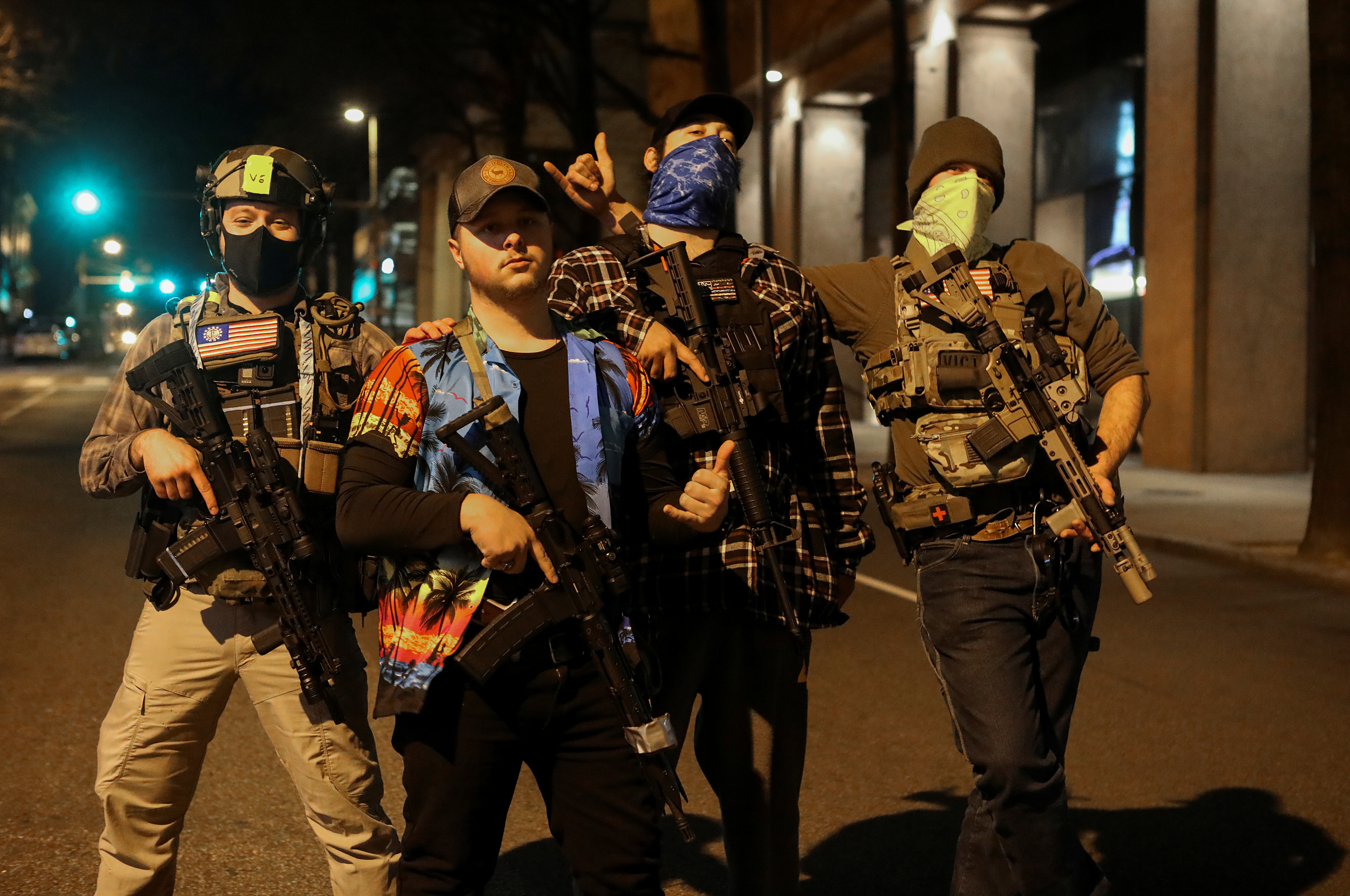 Mike Dunn, second from left, and other members of the Boogaloo Boys movement, pose for photos with their semi-automatic rifles, days ahead of President-elect Joe Biden inauguration, in Richmond, Virginia, U.S. January 17, 2021. REUTERS/Jim Urquhart
