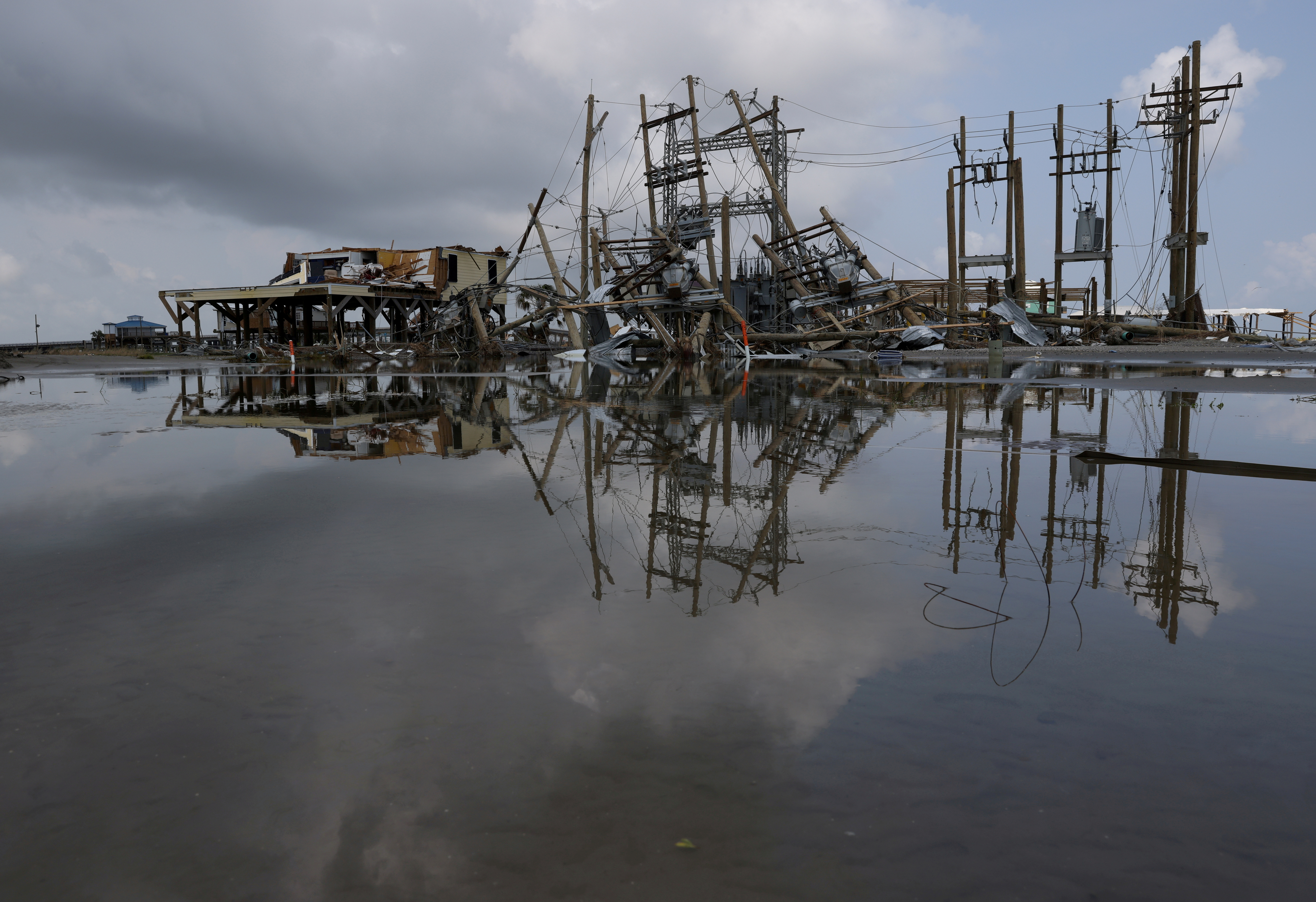 Damaged power lines and homes can be seen days after hurricane Ida ripped through Grand Isle, Louisiana, U.S., September 2, 2021. REUTERS/Leah Millis/File Photo