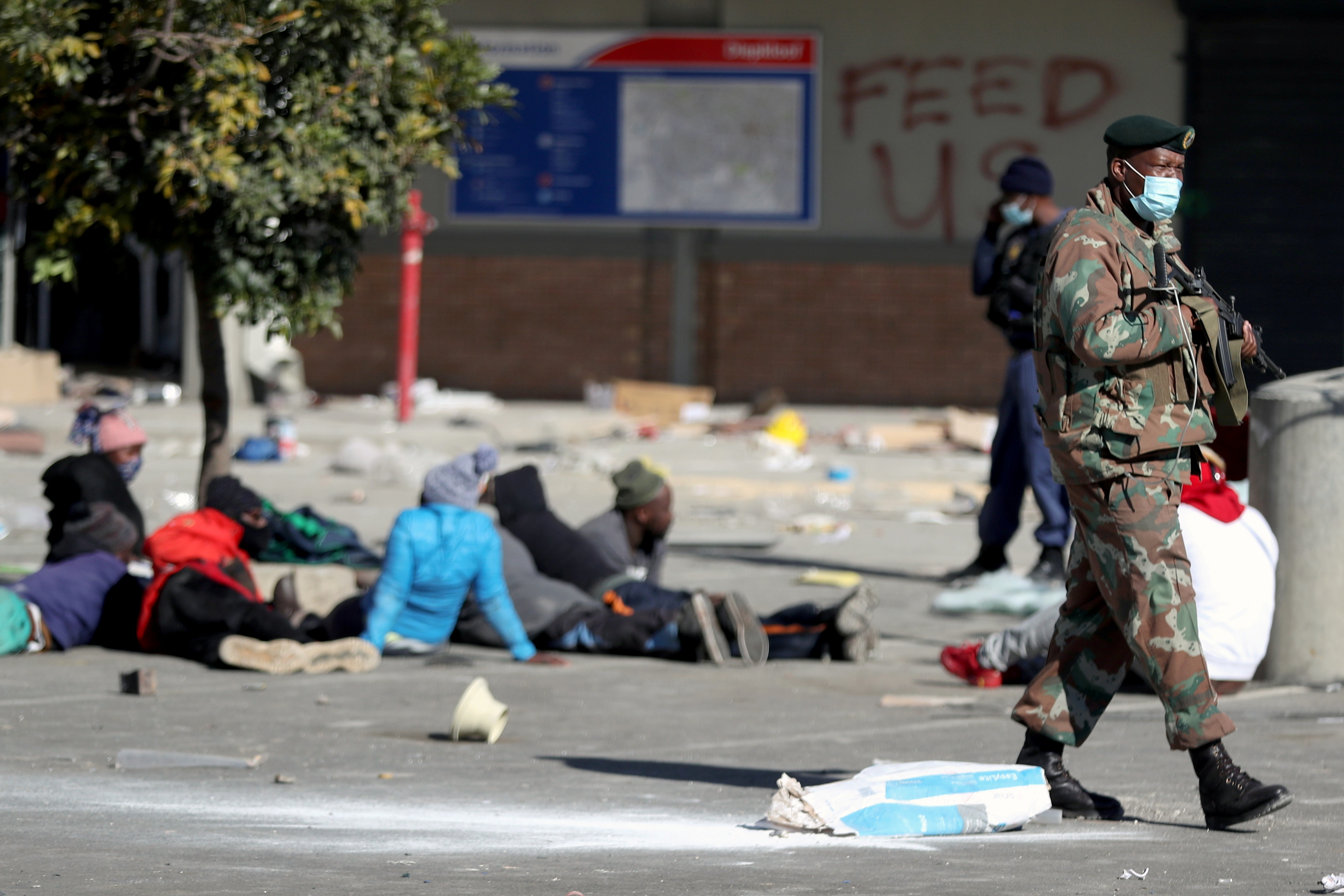 A member of the military keeps guard next to suspected looters outside Diepkloof mall as the country deploys army to quell unrest linked to jailing of former President Jacob Zuma, in Soweto, South Africa, July 13, 2021. REUTERS/Siphiwe Sibeko